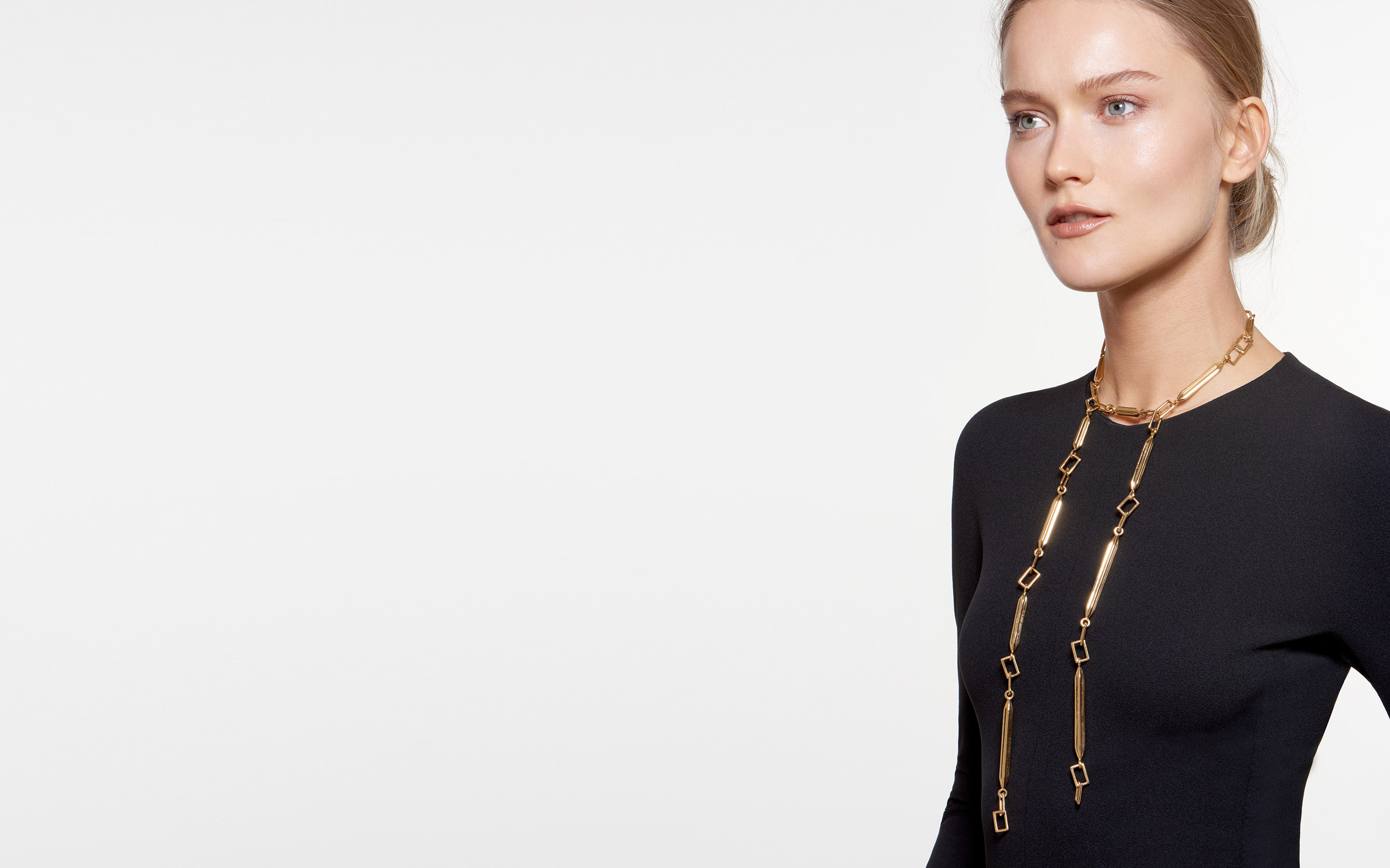 bold blonde woman modeling 22 karat gold necklace made of angular links