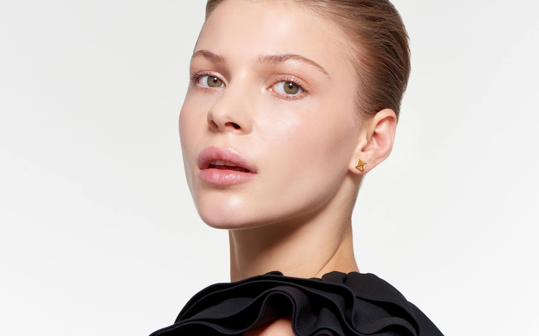 shining cage stud earrings 22 karat polished gold on striking woman