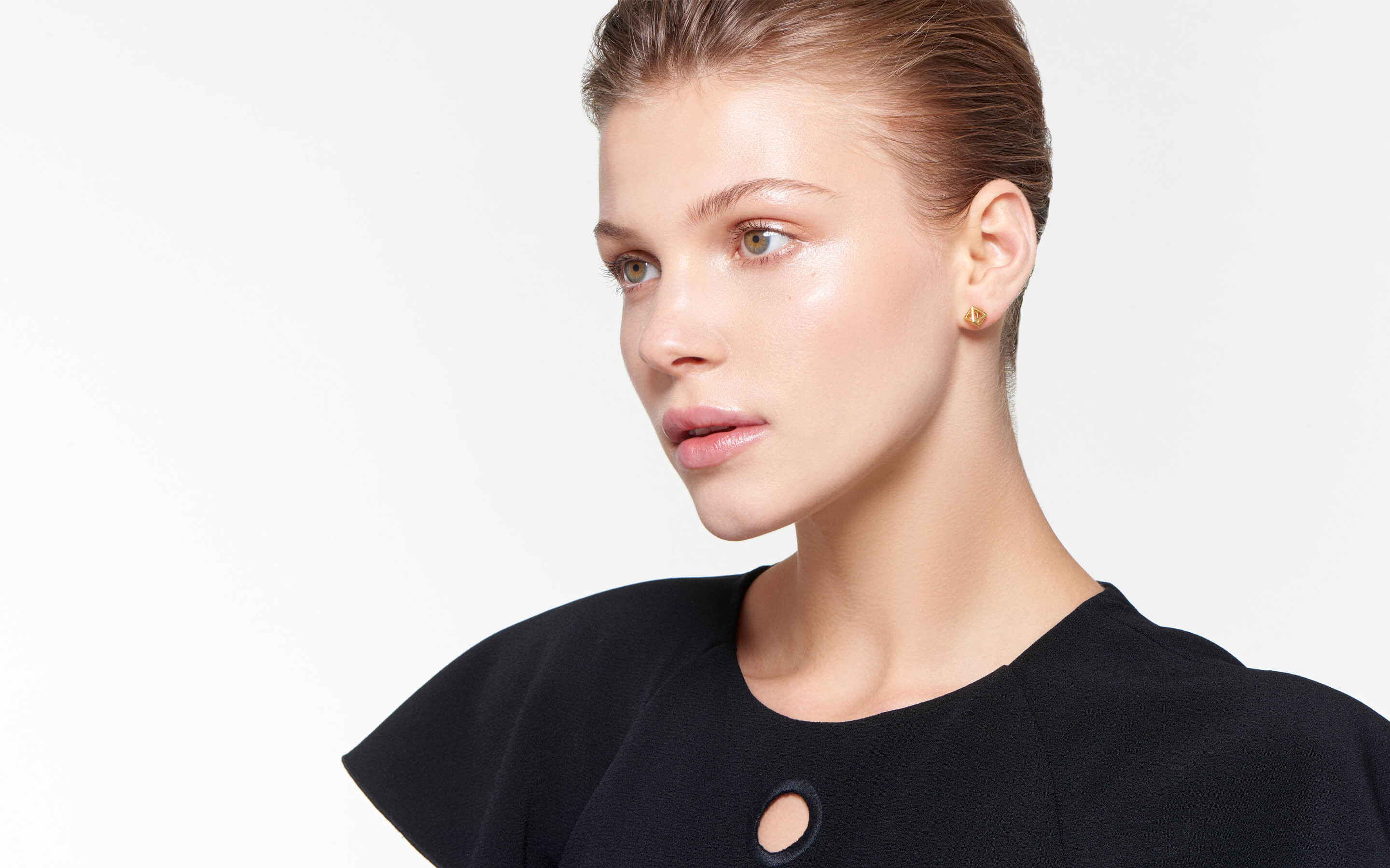 model with contemplative expression wearing dainty 22 karat polished gold earrings in cage design