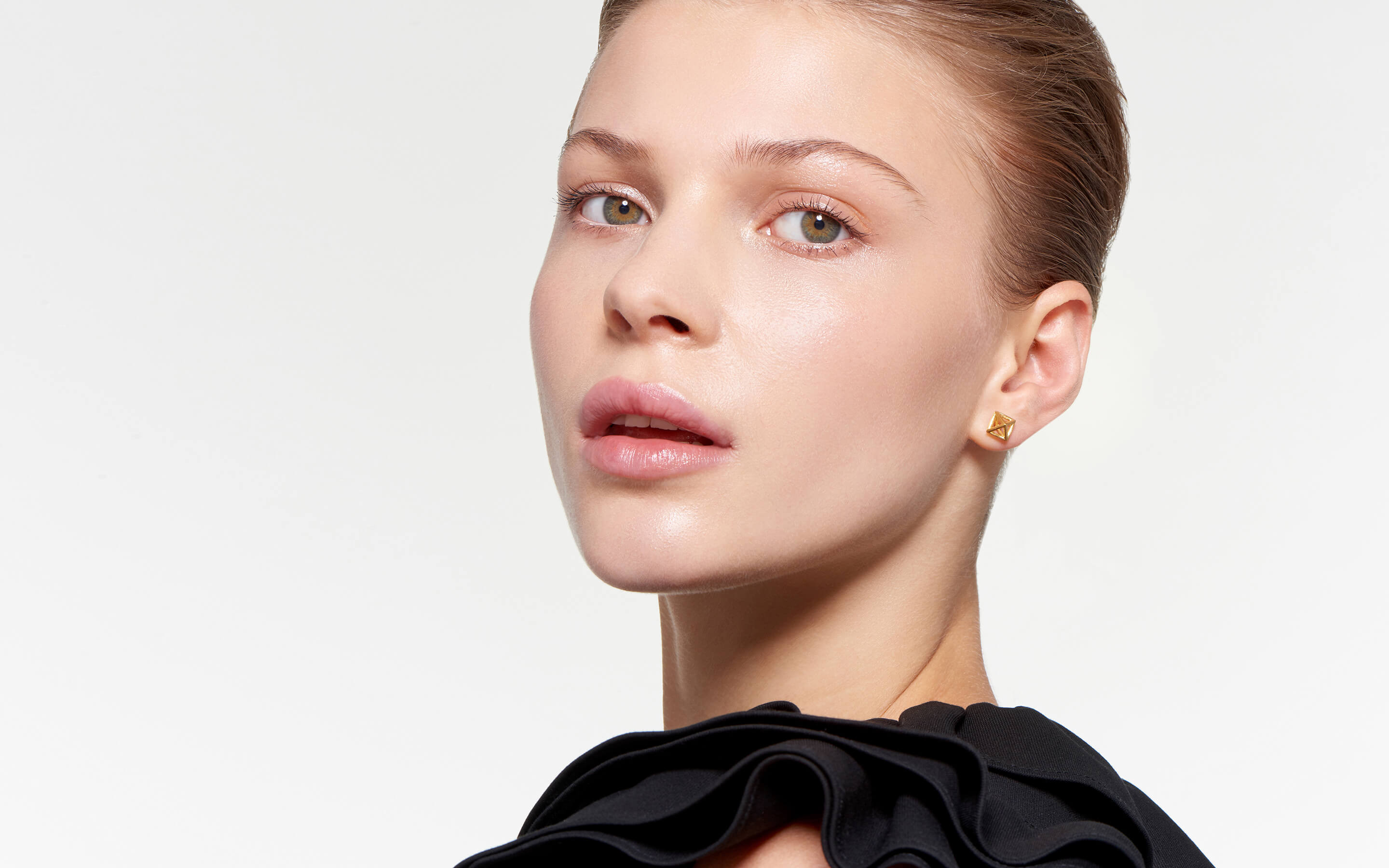 model adorned with burnished satin cage stud earrings in 22 karat gold