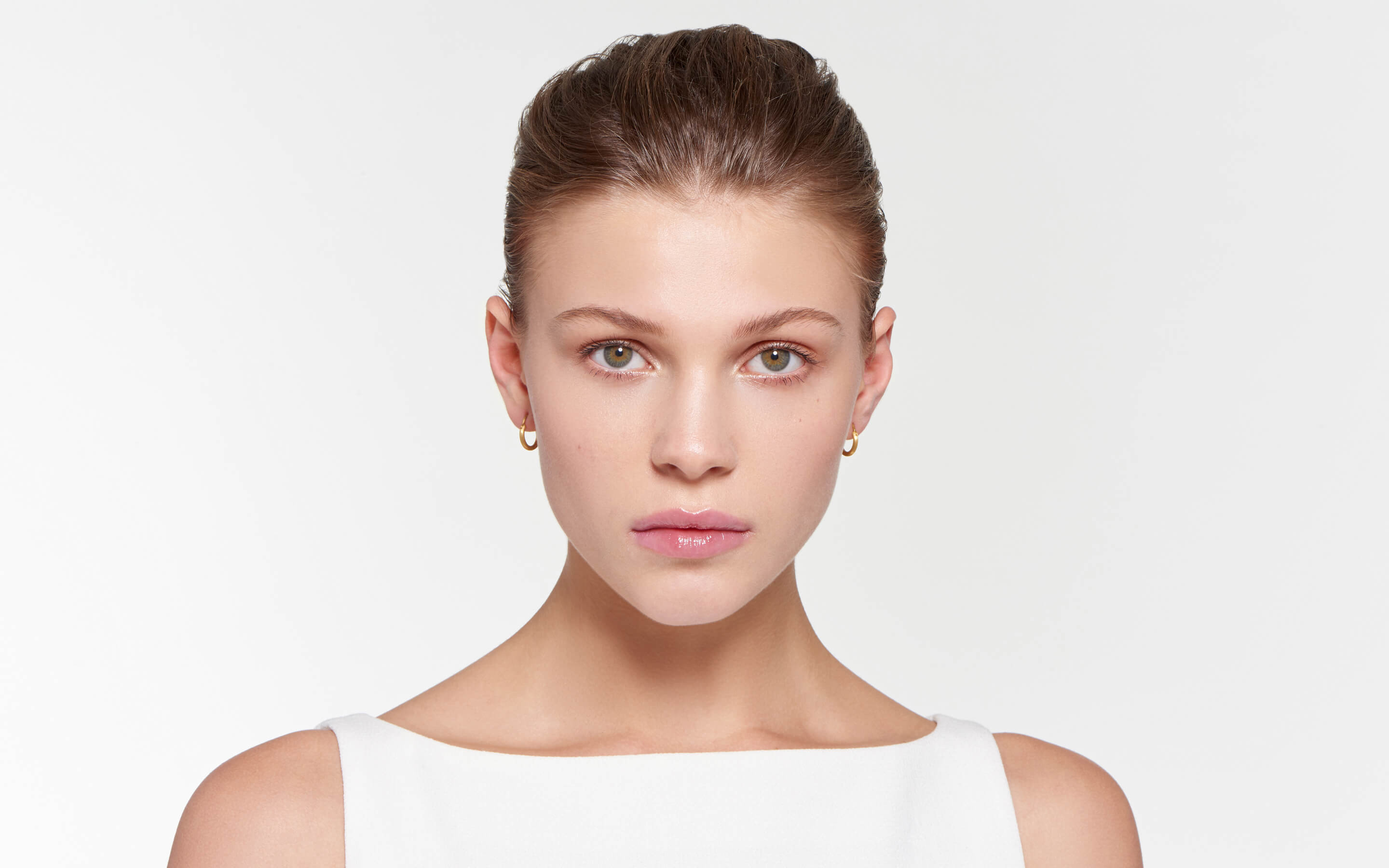 attractive model adorned with 22 karat gold hoop earrings in satin finish