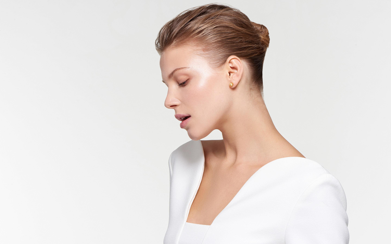 captivating model wearing spherical 22 karat gold stud earrings in satin finish