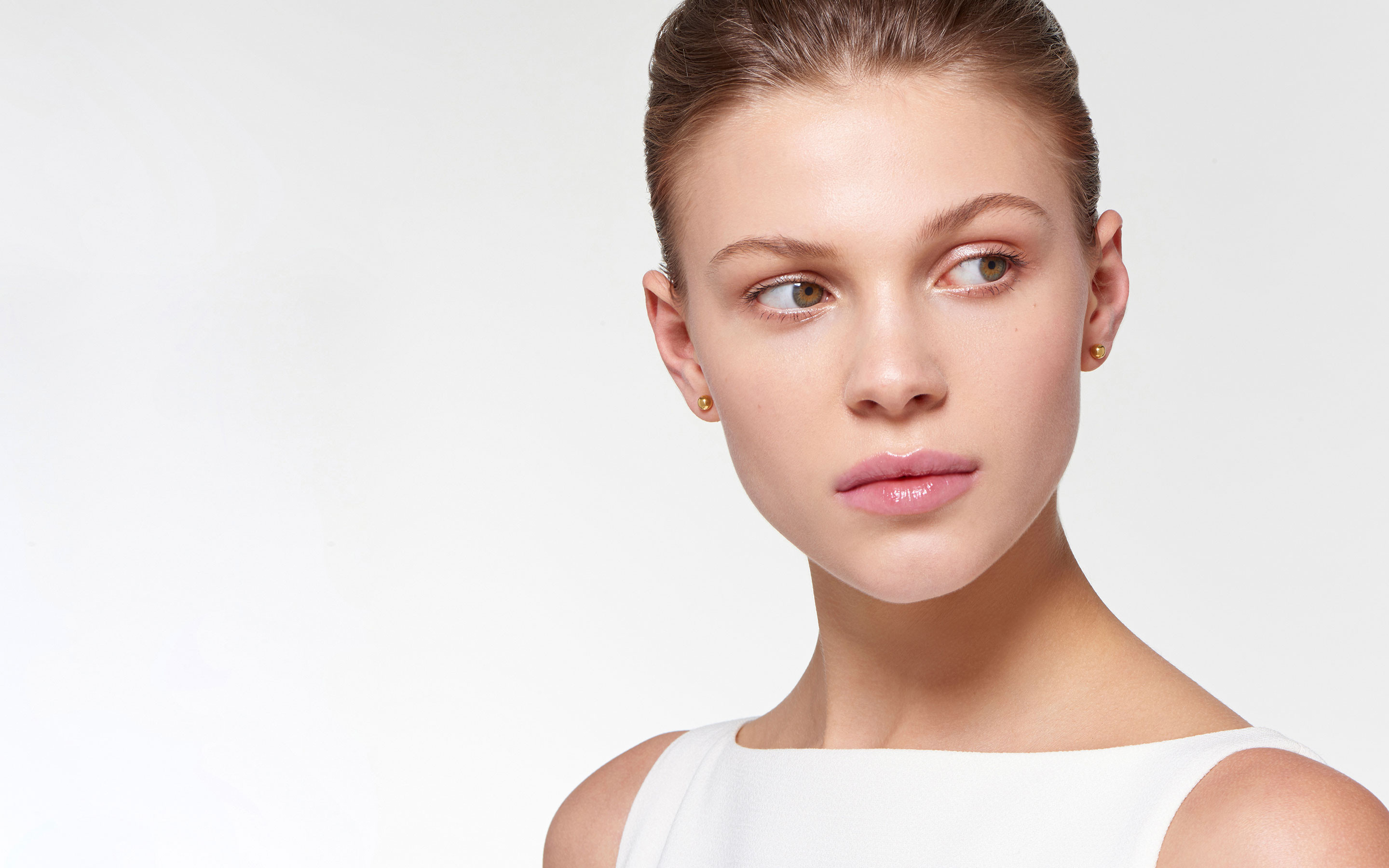 beautiful model with sparkling globe stud earrings of 22 karat polished gold