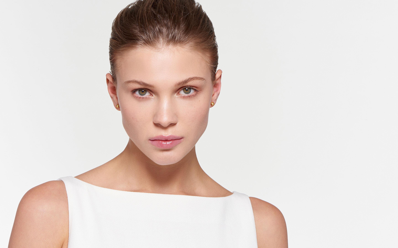 beautiful model wearing burnished stud earrings of 22 karat gold satin finish
