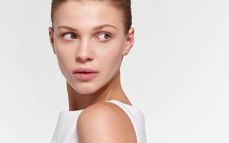 alluring woman modeling globular 22 karat gold stud earrings