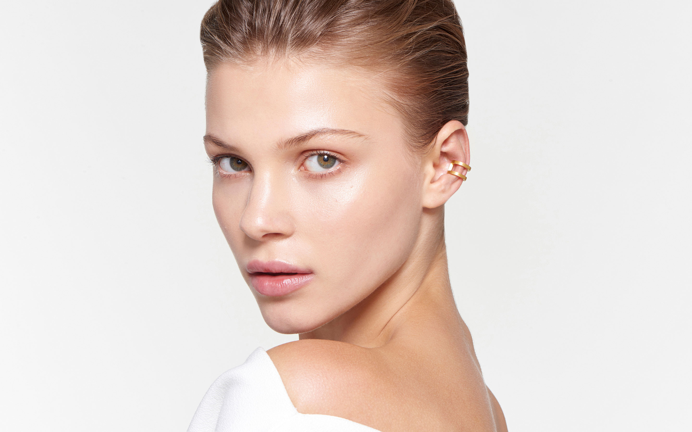 elegant female model wearing stylish 22 karat gold ear cuffs in satin finish