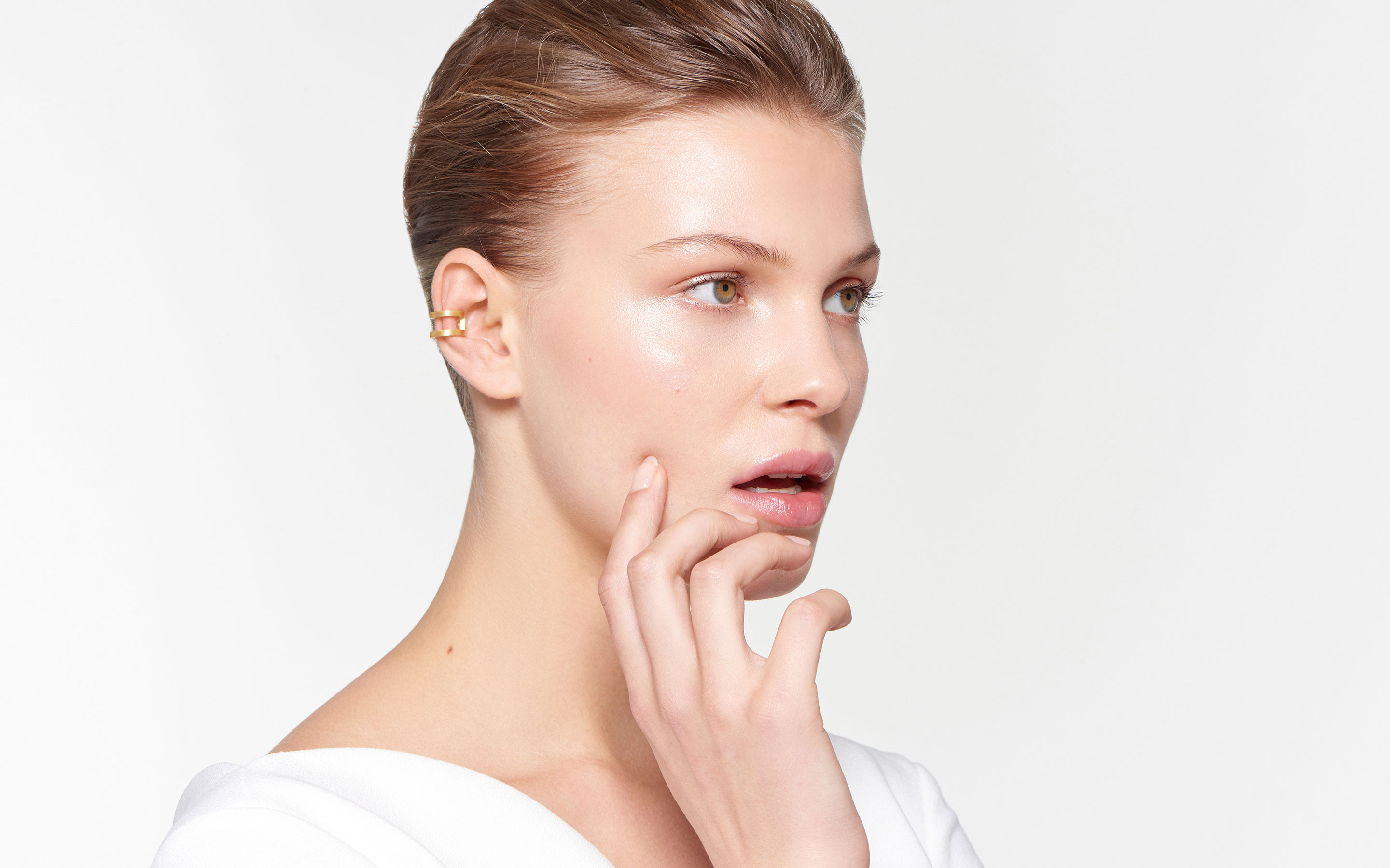 stylish model showcasing abstract ear cuff made of 22 karat satin gold