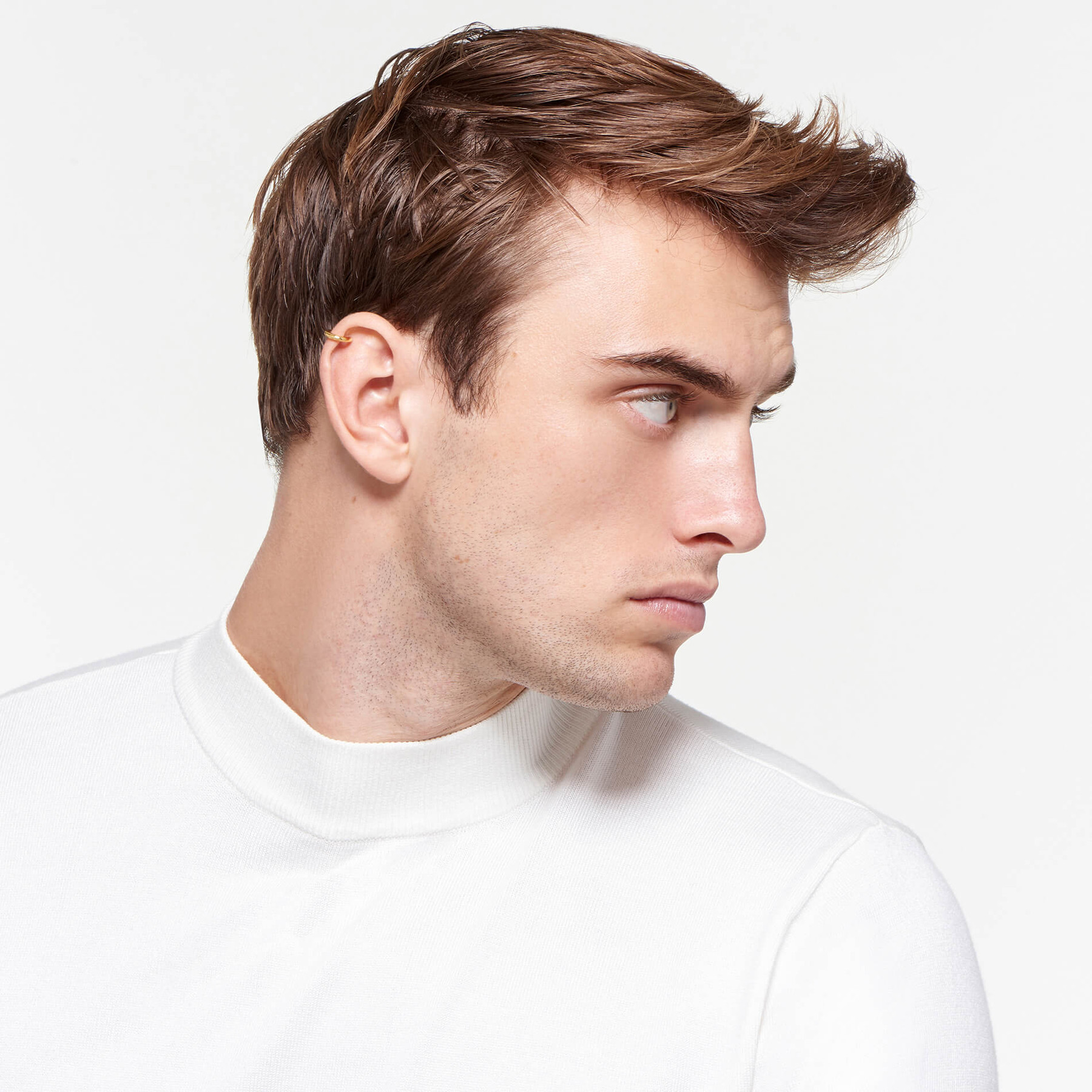 22 karat polished gold ear cuff worn by brooding male model in profile