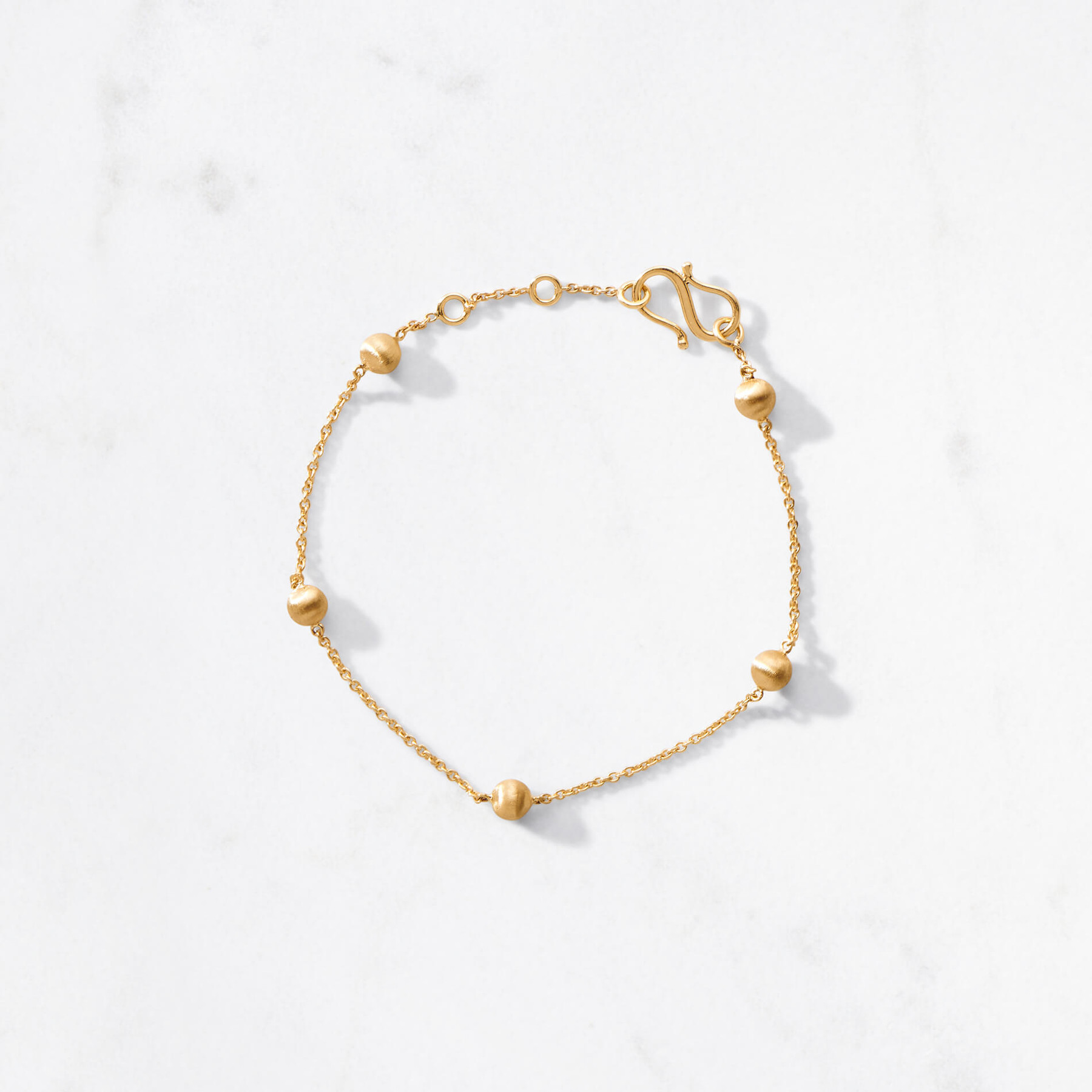 Delicate mini moons orbit your wrist with grace. Handcrafted from 22 karat satin finished gold with an adjustable chain and an approximate gold weight of 4.5 grams, Pavo Bracelet goes full circle.