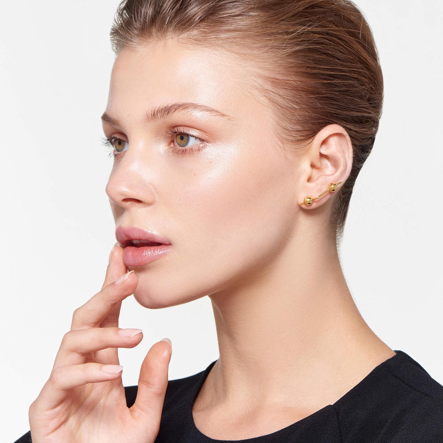 attractive model wearing modern 22 karat polished gold earrings in zigzag pattern