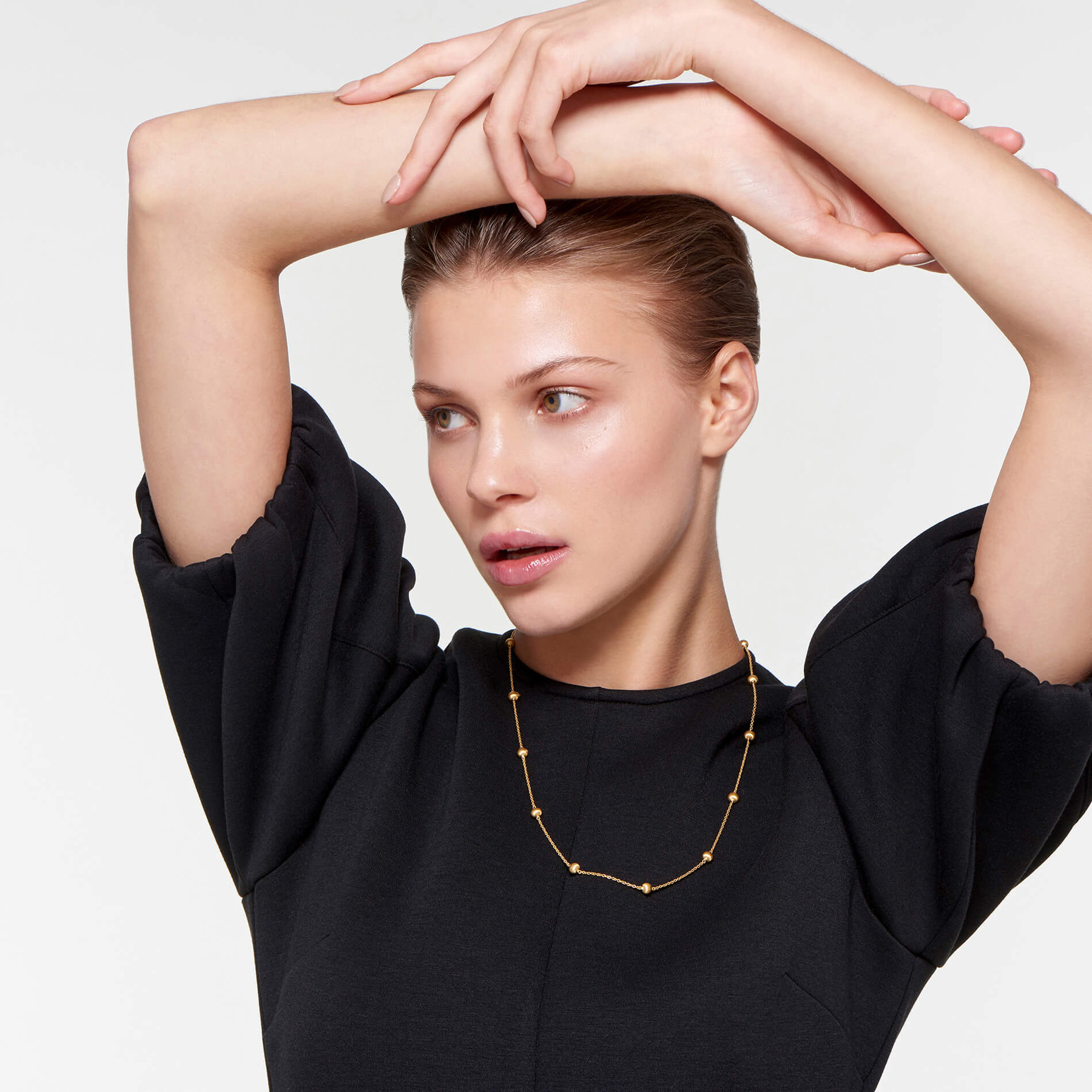 graceful woman modeling 22 karat gold necklace with small spheres in orbital pattern