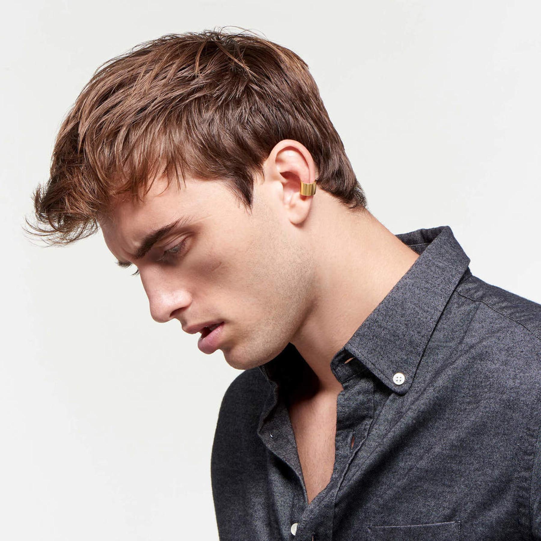 dashing male model wearing glimmering ear cuff of 22 karat polished gold