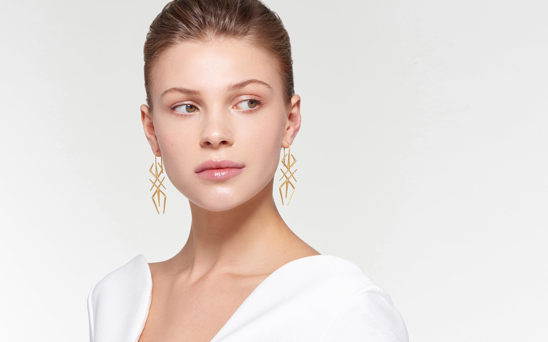 ethereal female model adorned with modish arthropod 22 karat gold earrings