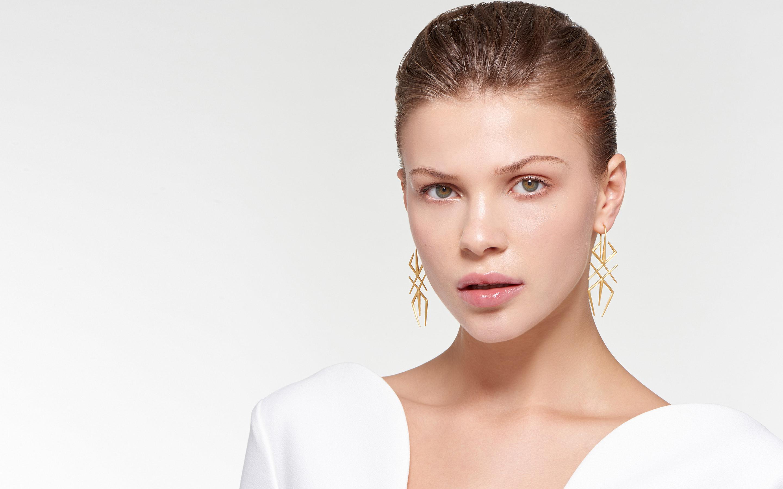 striking model wearing 22 karat satin gold earrings in modern arthropod-inspired design