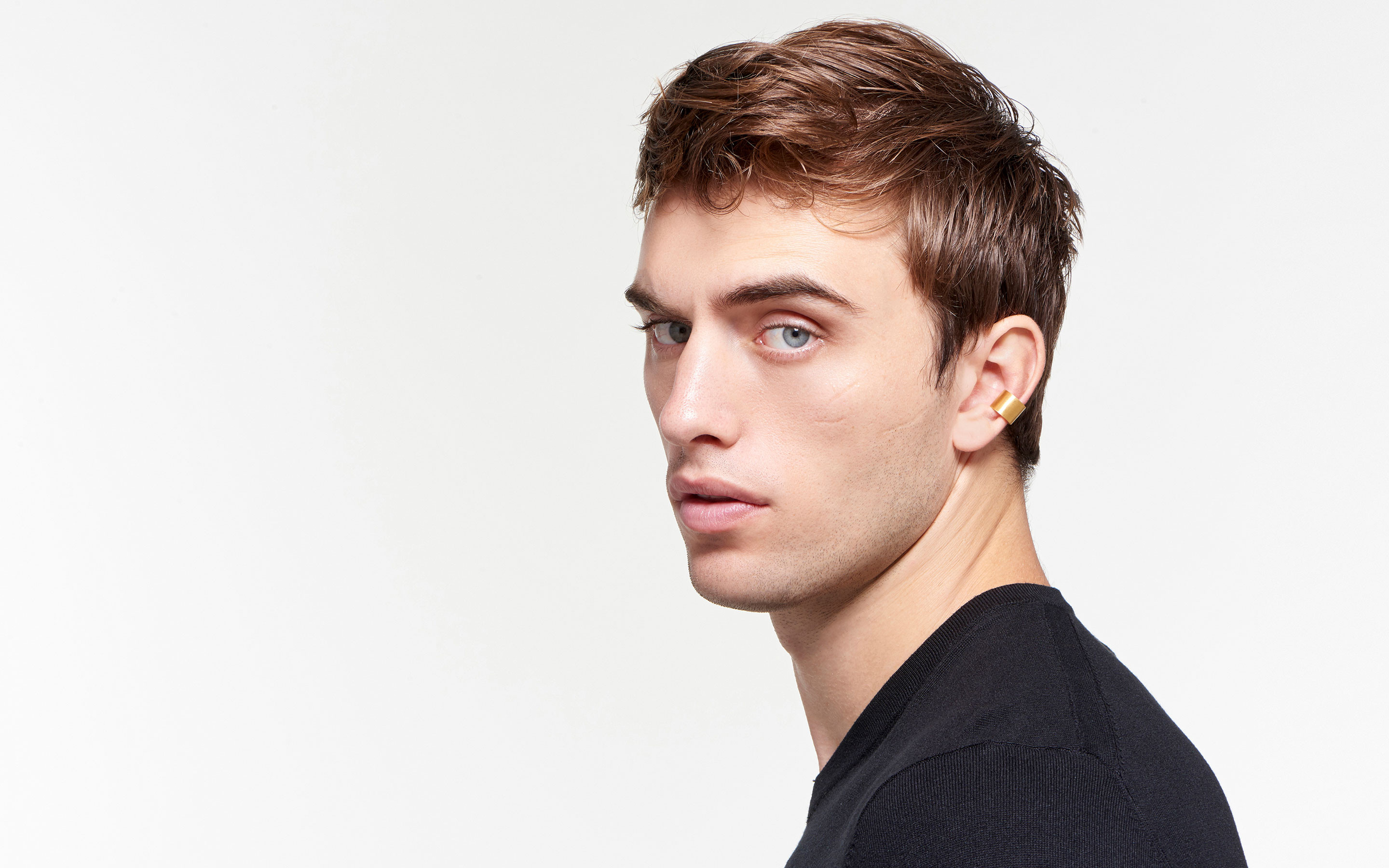 22 karat gold ear cuff in crescent shape on attractive male model staring stoically