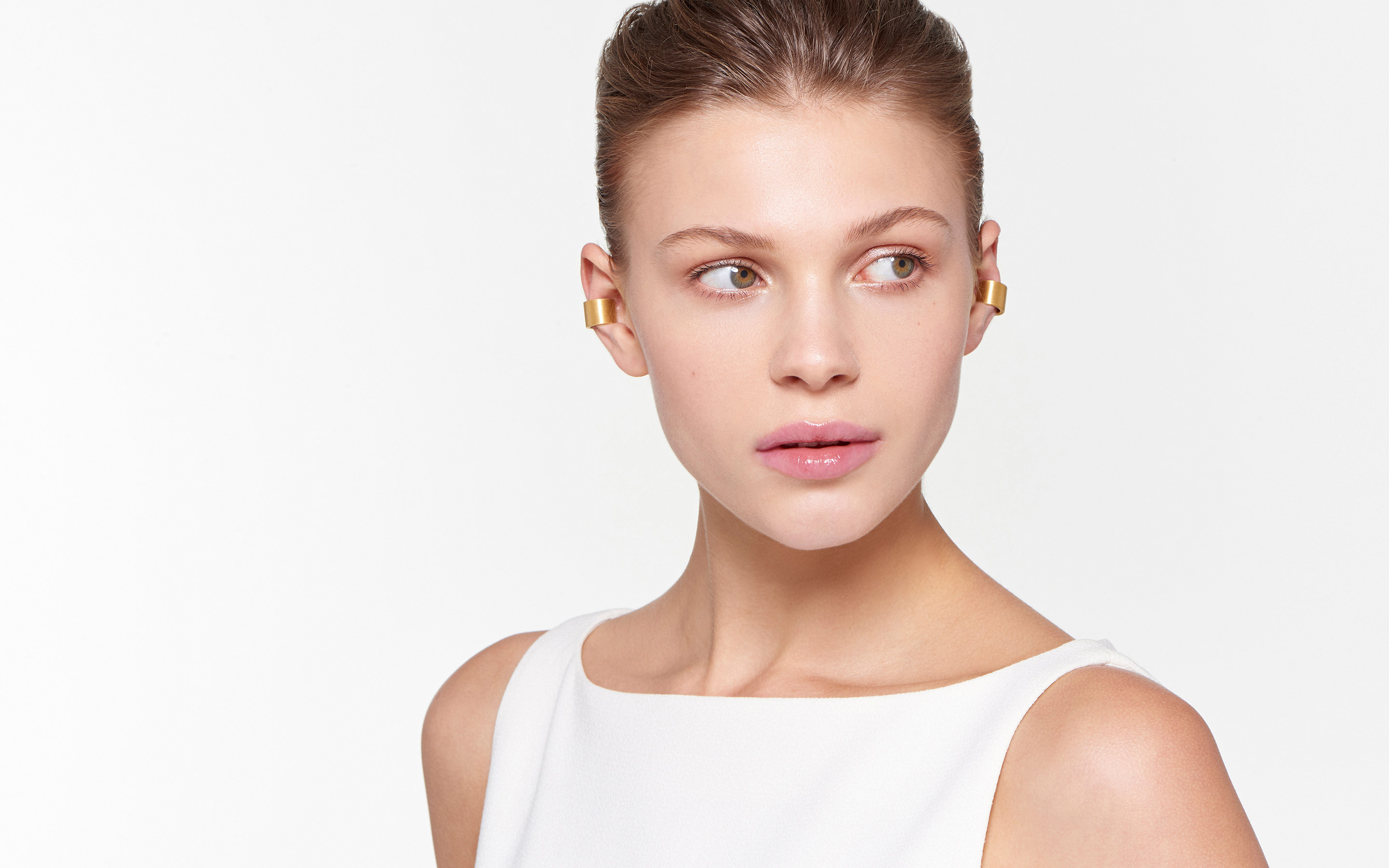 lovely female model glancing sideways wearing vibrant 22 karat gold ear cuffs in satin finish
