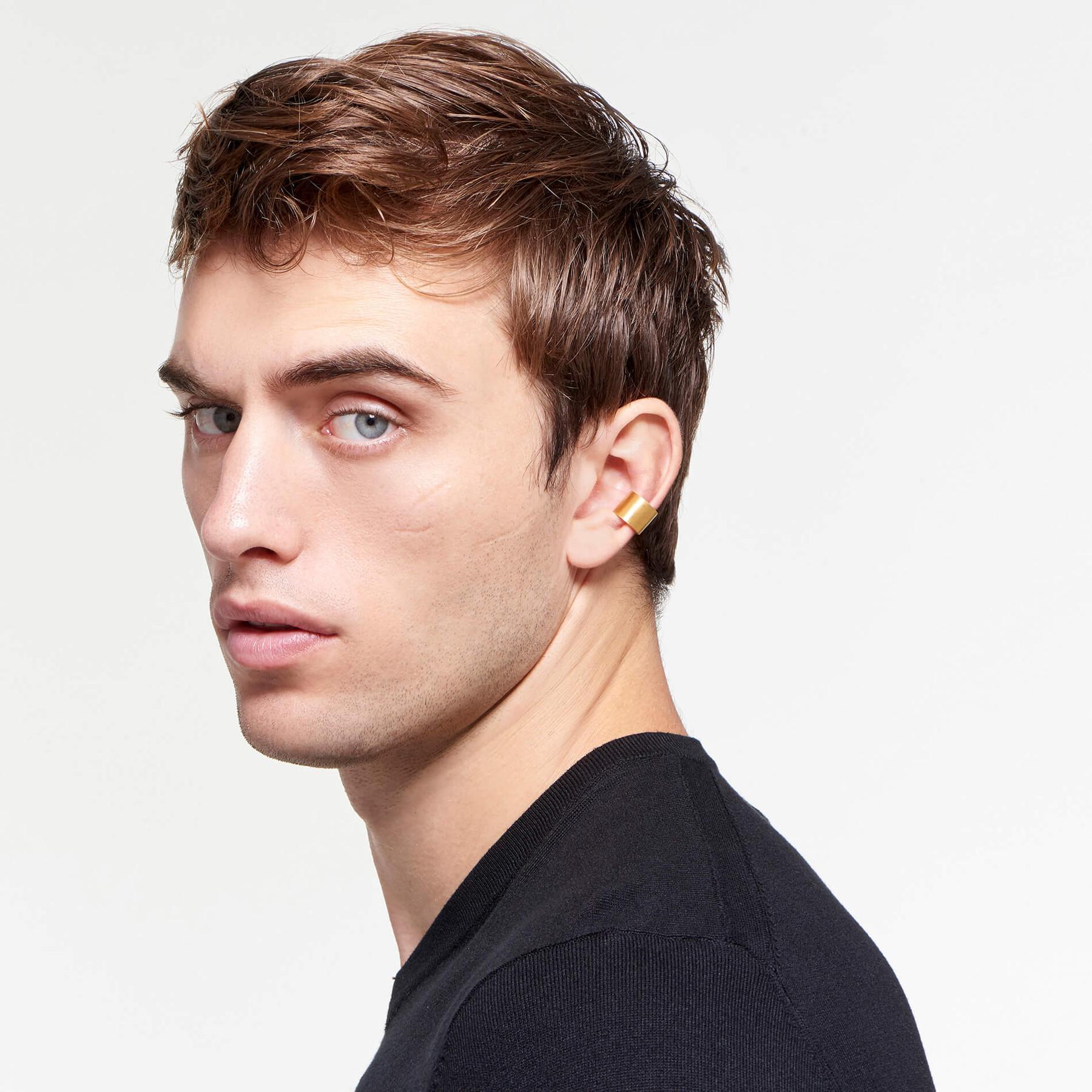 intense male model wearing satin 22 karat gold ear cuff