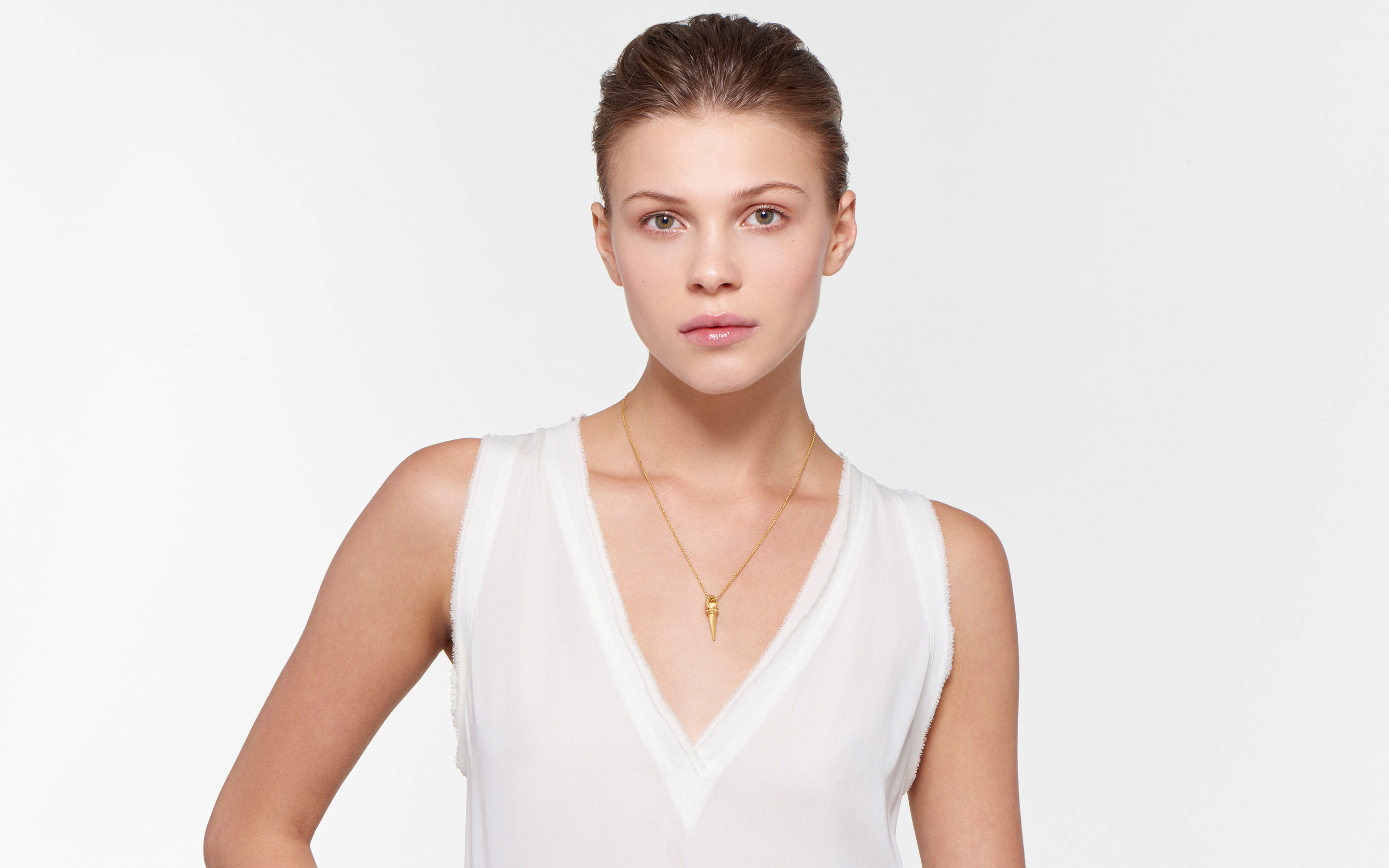 lithe model exhibiting 22 karat gold necklace with small cone charm in satin finish