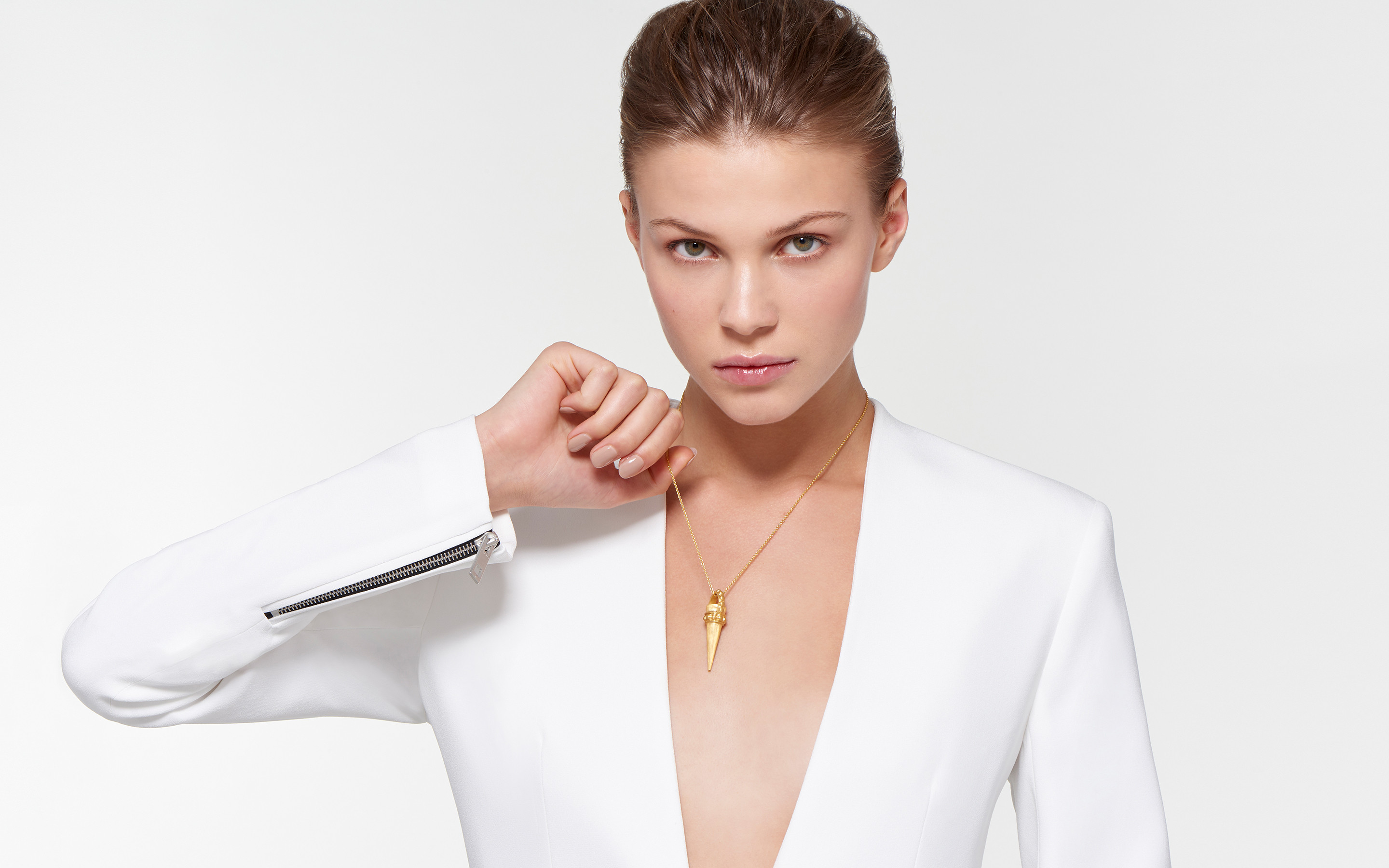 glamorous model showcasing 22 karat gold necklace with modern cone amulet in satin finish