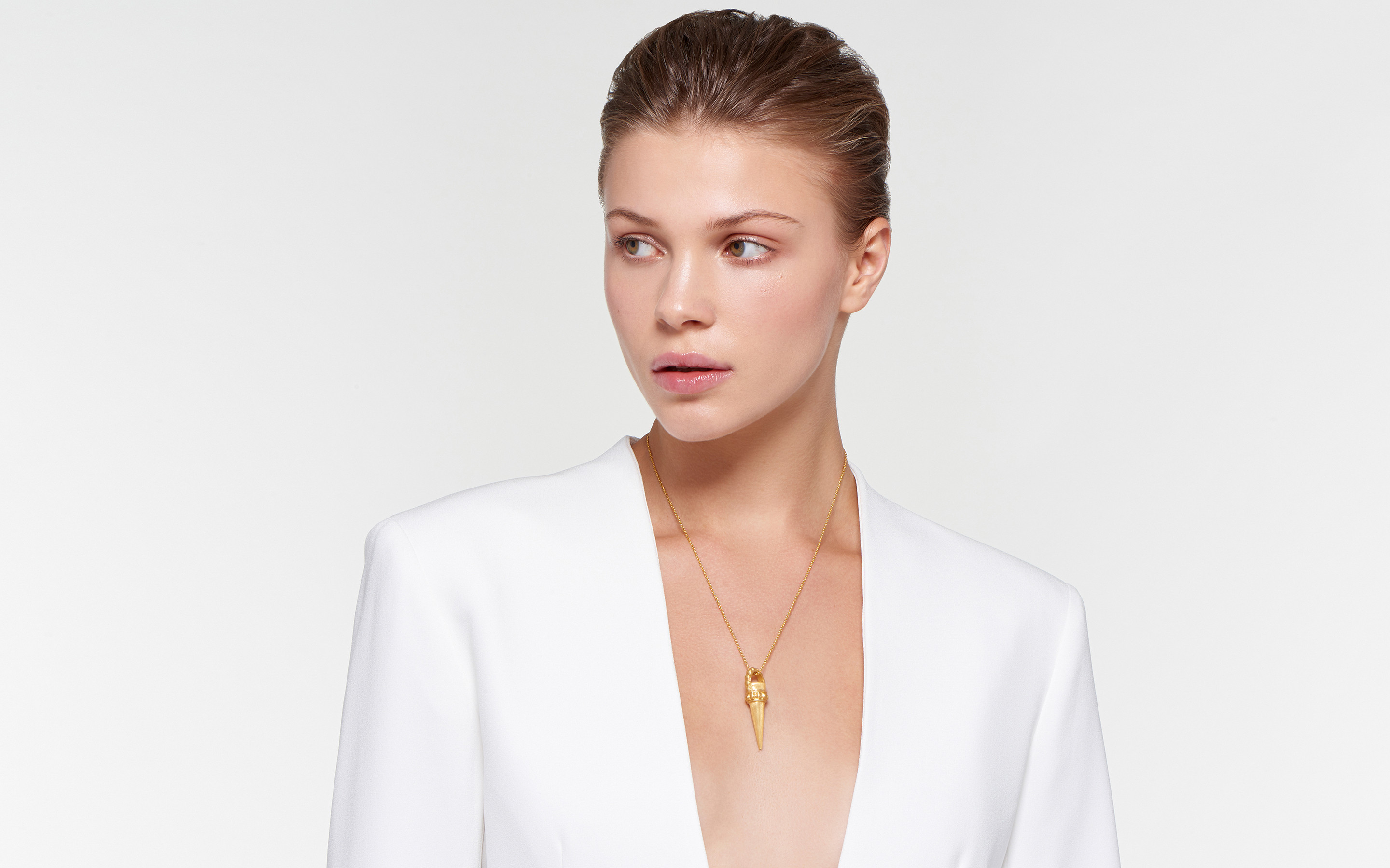 stylish model wearing 22 karat gold necklace with avant garde cone pendant in satin finish