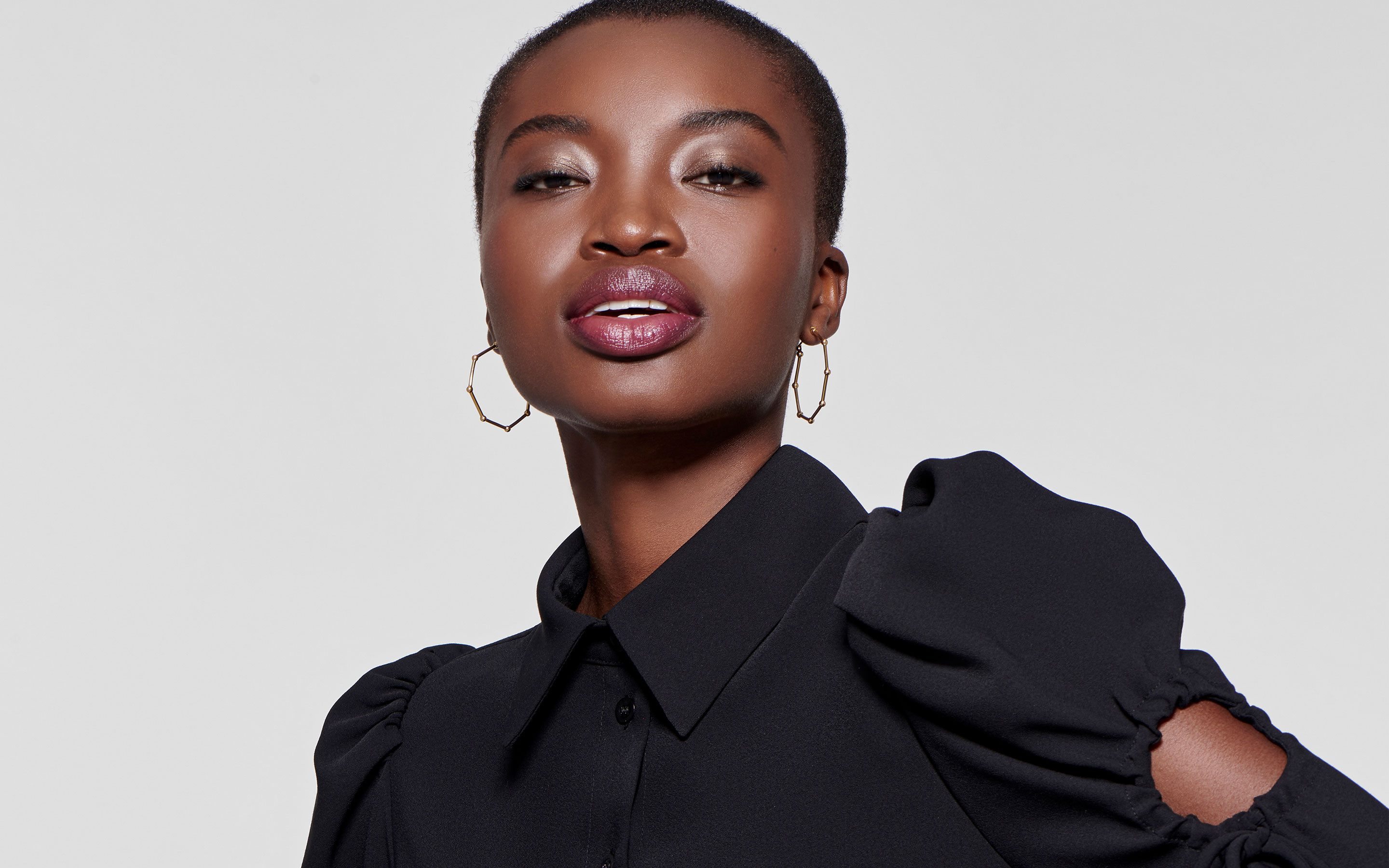 captivating black woman modeling hexagonal hoop earrings of 22 karat gold in polished finish