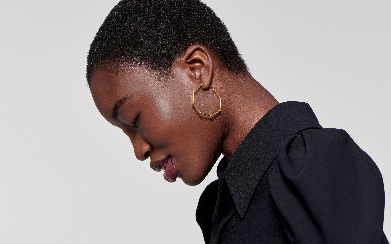 pretty black model in reflective pose wearing 22 karat gold geometric hoop earrings