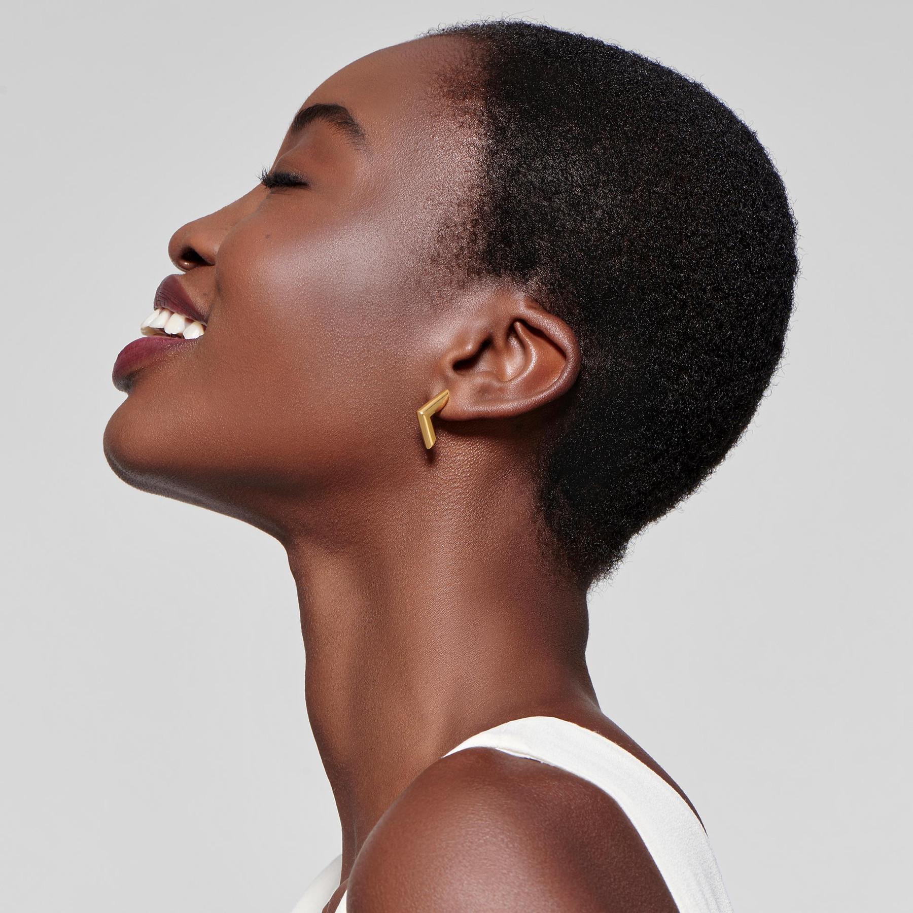 smiling black model in profile displaying 22 karat gold earrings in angular design