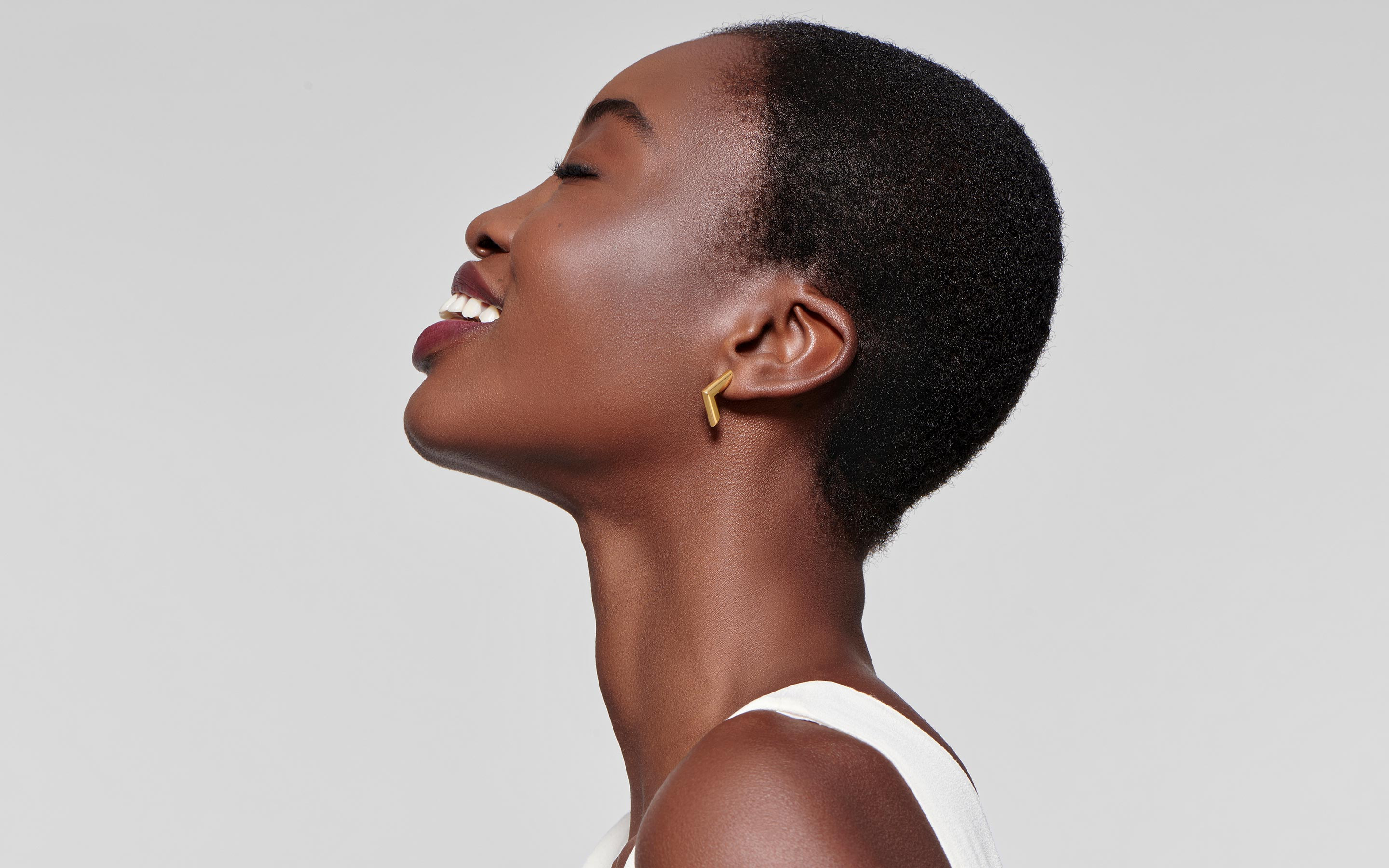 side shot of delighted black woman modeling pointed earrings made of 22 karat gold in polished finish
