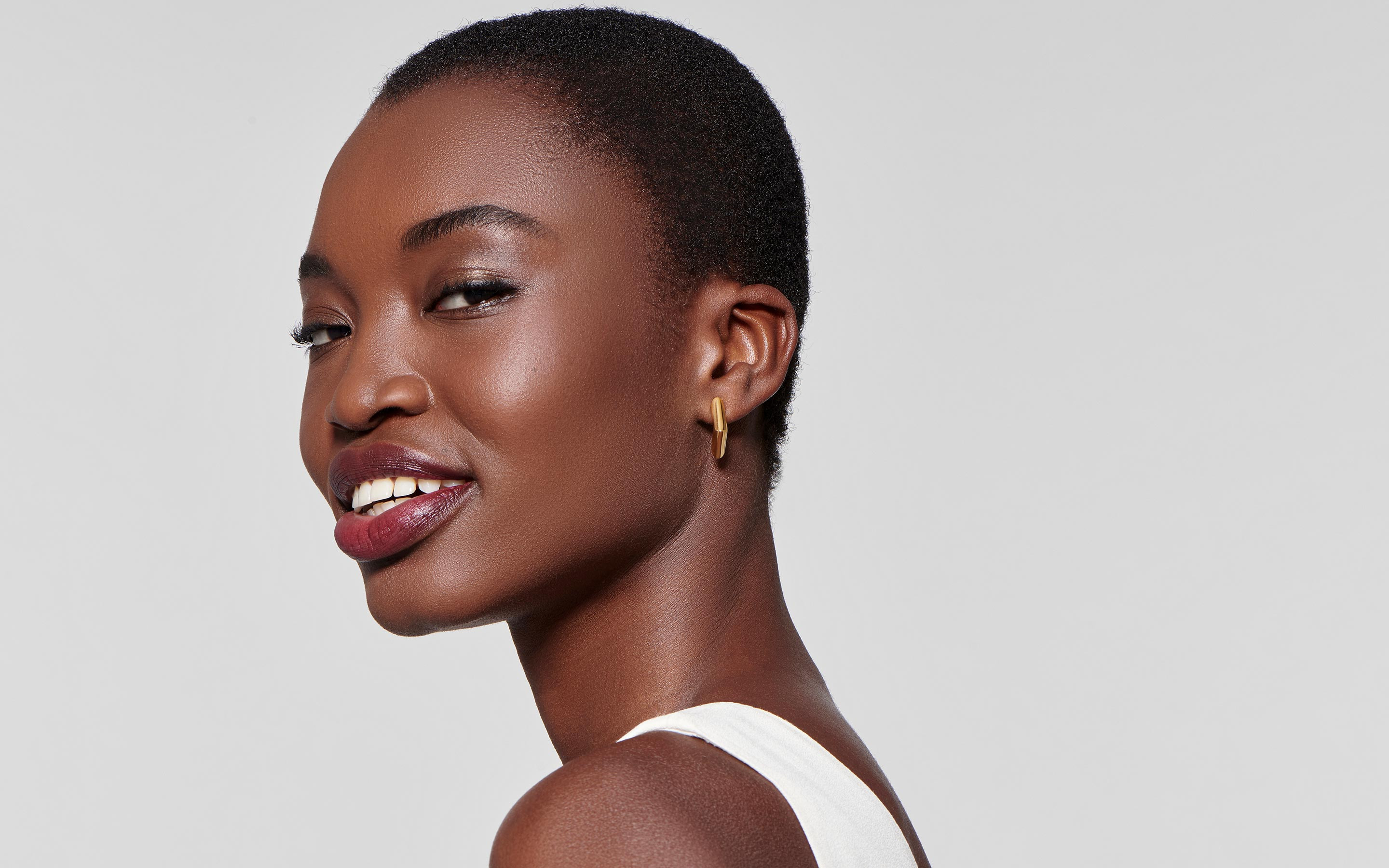 alluring black female model with glowing contemporary 22 karat gold earrings in valley shape