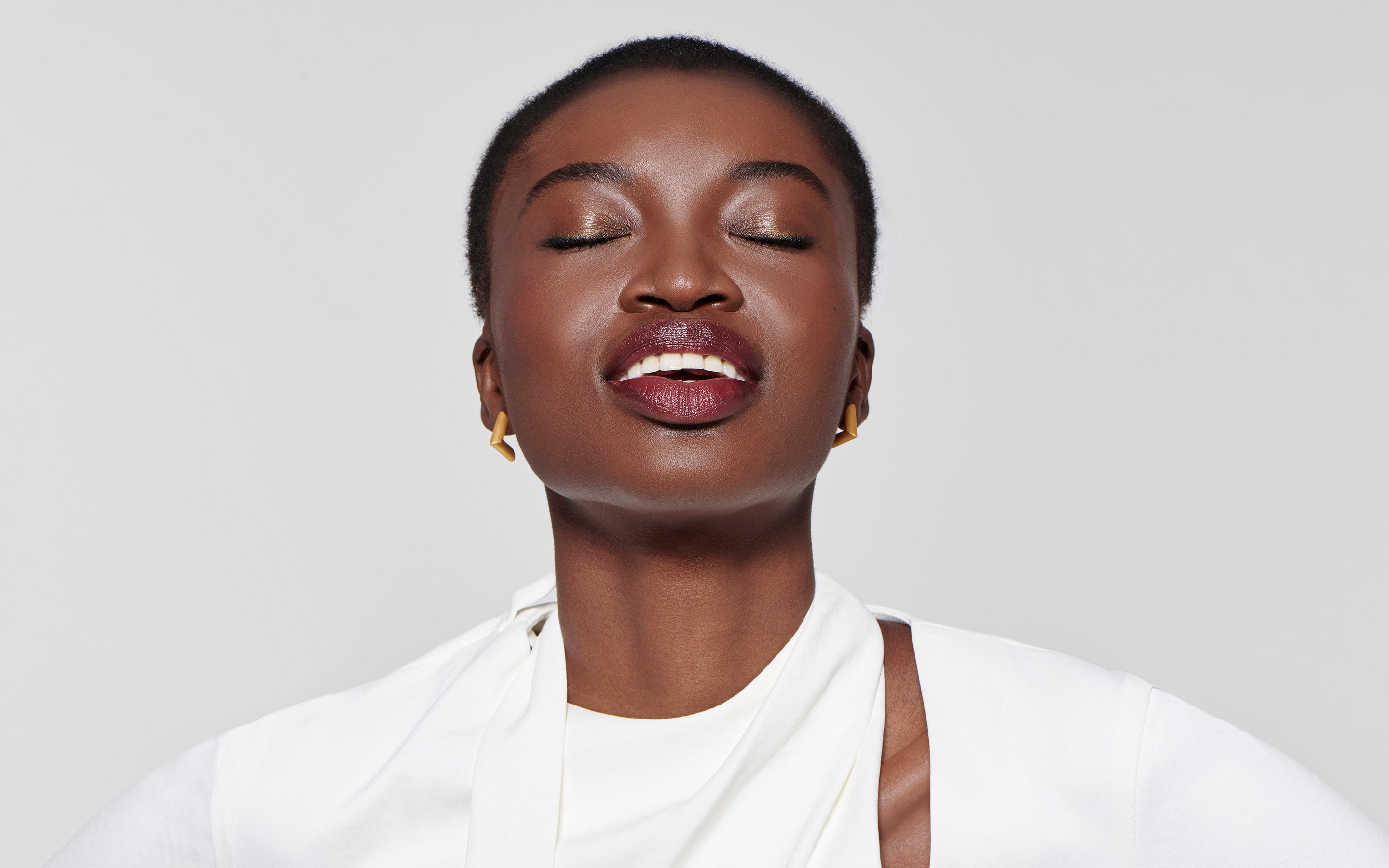 good-looking black model with calm smile wearing angular earrings of 22 karat gold
