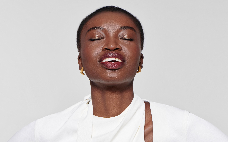 good-looking black model with calm smile wearing angular earrings of 22 karat gold