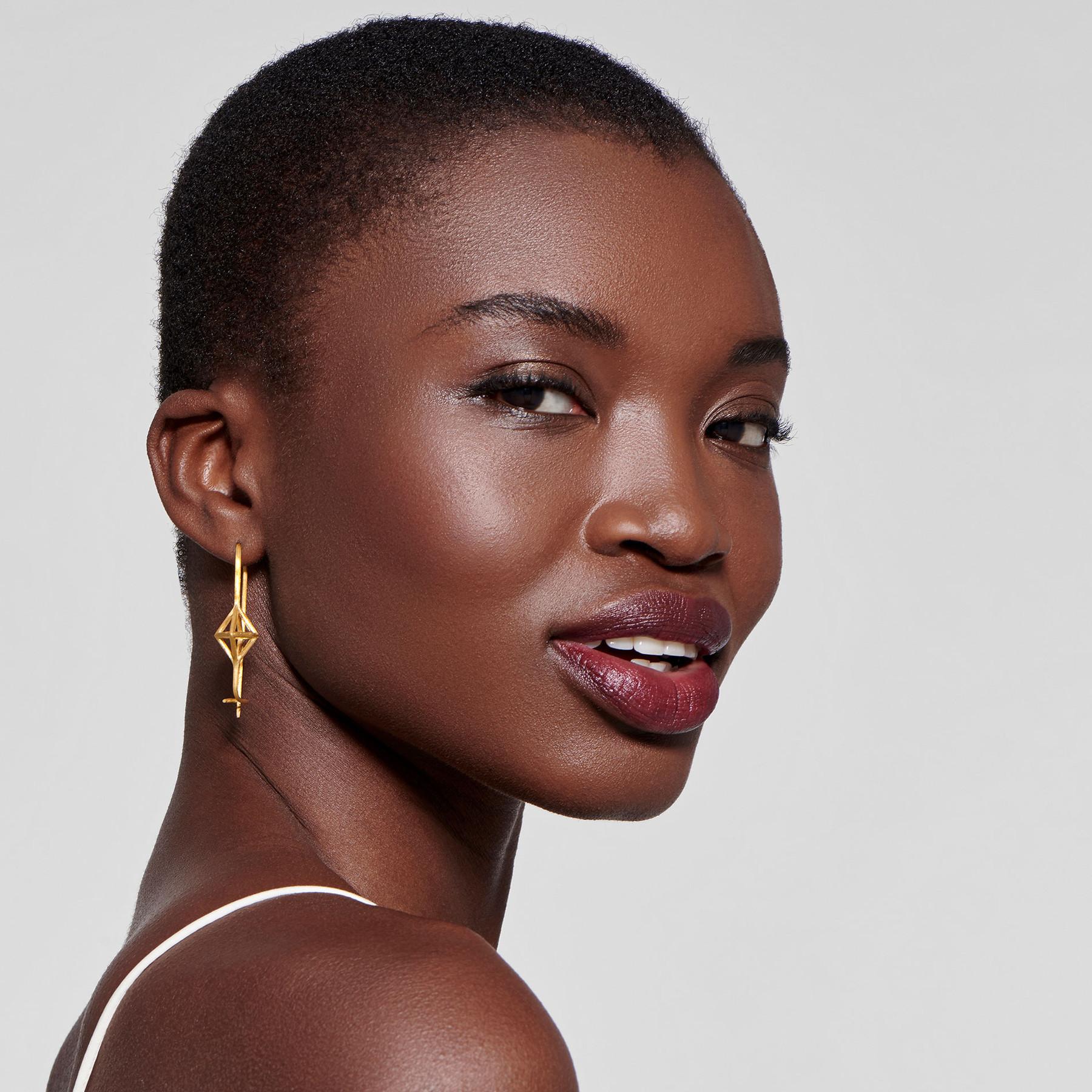 lovely black model gazing to the side wearing cage hook earrings in 22 karat satin gold