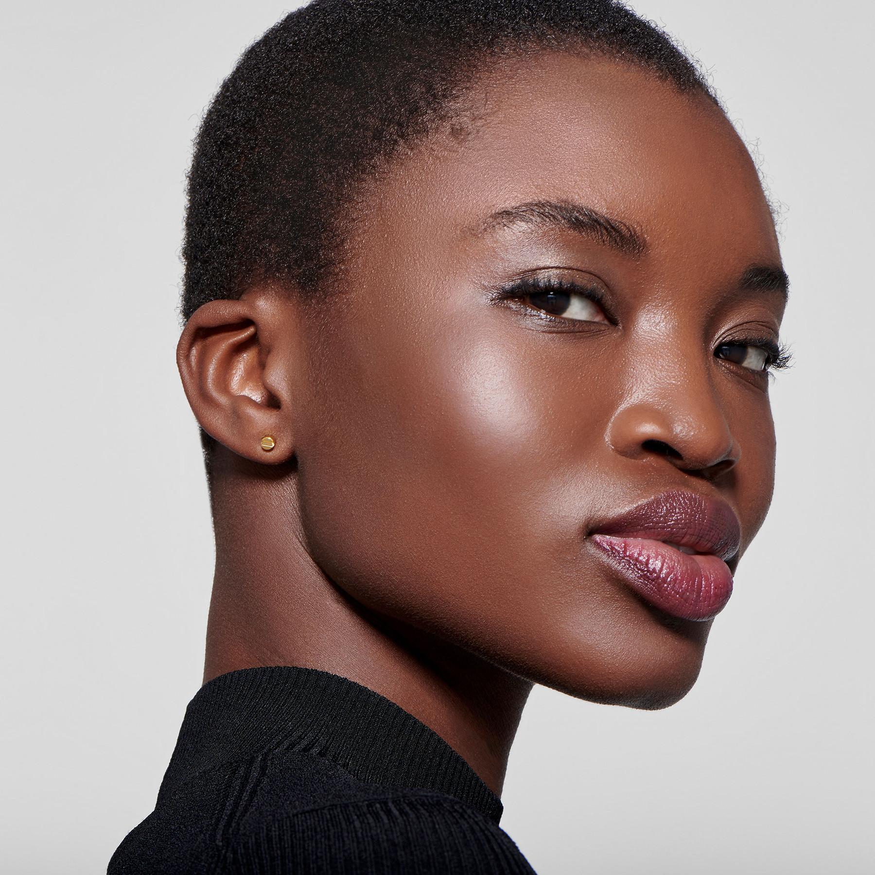 22 karat gold stud earrings on attractive black female model