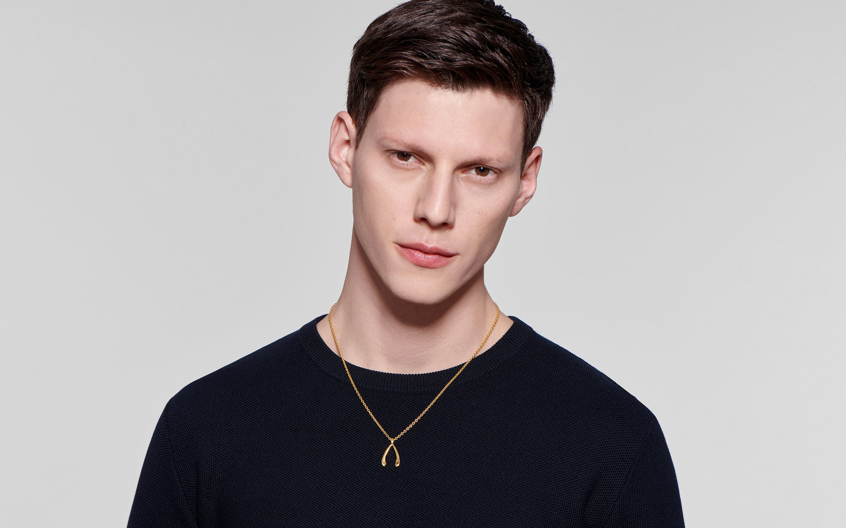 smoldering male model wearing 22 karat gold necklace with wishbone pendant