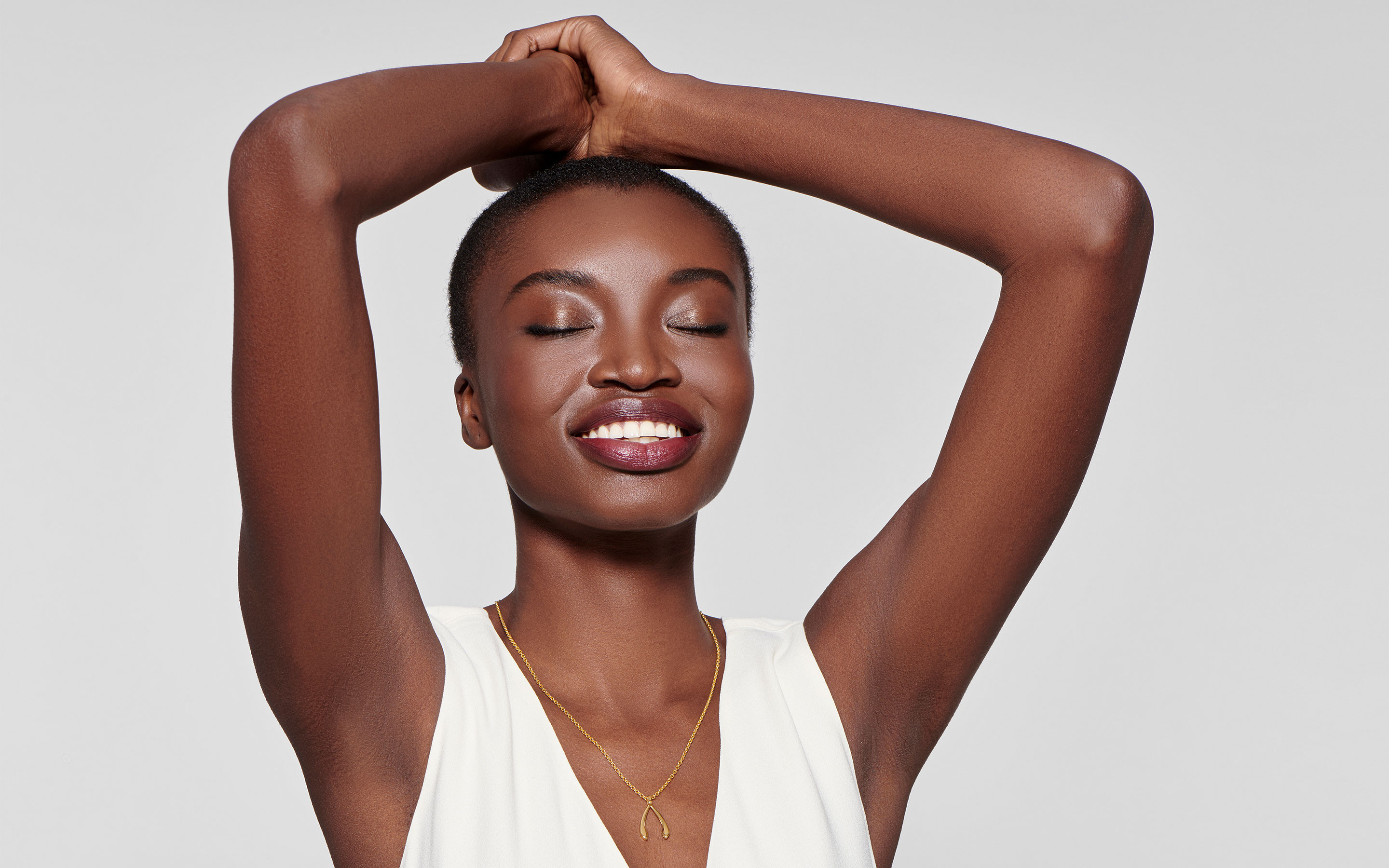 cheerful black woman modeling 22 karat gold necklace with wishbone pendant