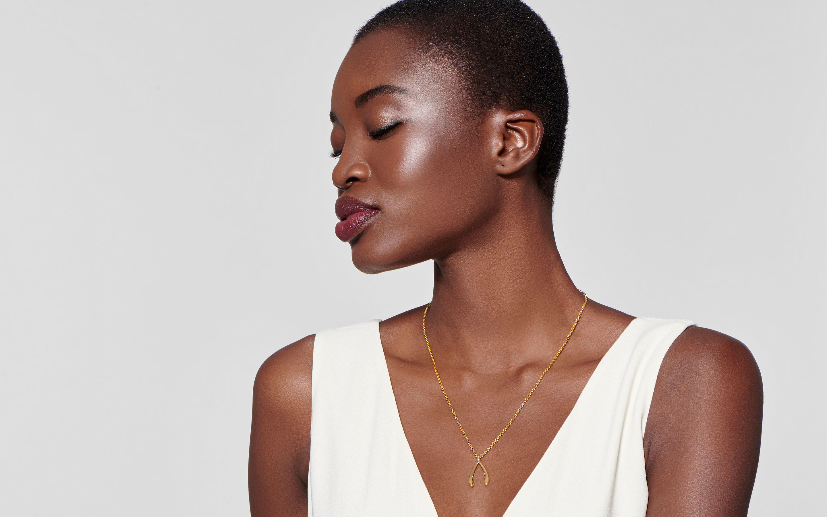 glamorous black model in profile showcasing 22 karat gold necklace wishbone charm