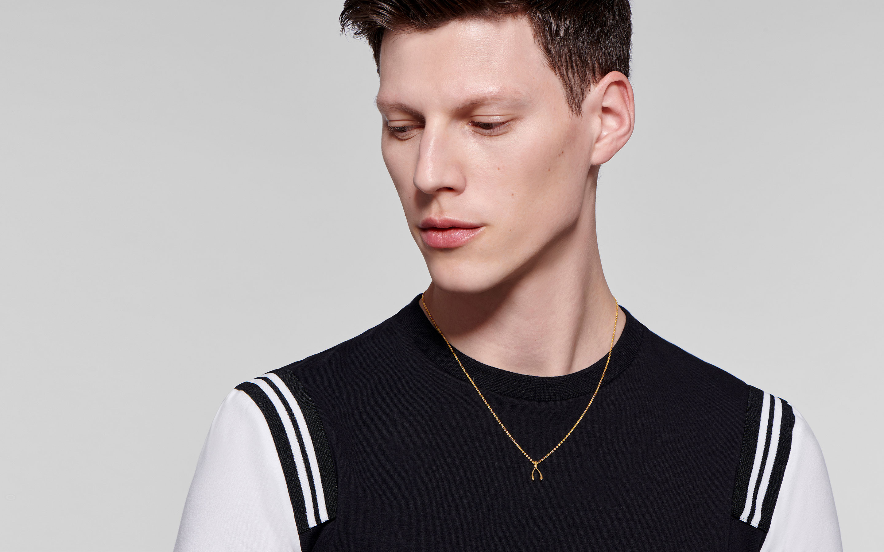 22 karat gold necklace with wishbone pendant showcased by brooding male model