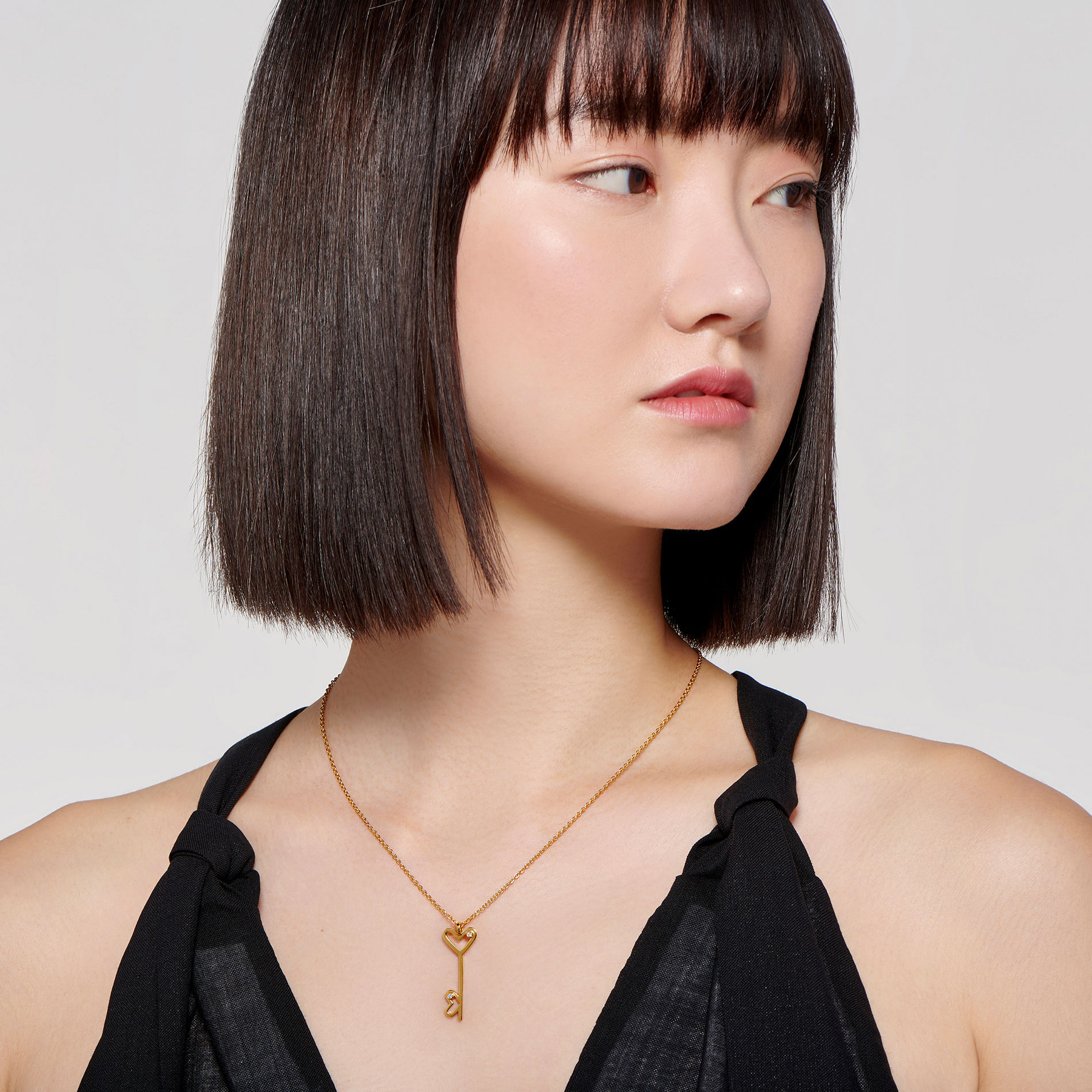 elegant East Asian model wearing 22 karat gold necklace with double key pendant