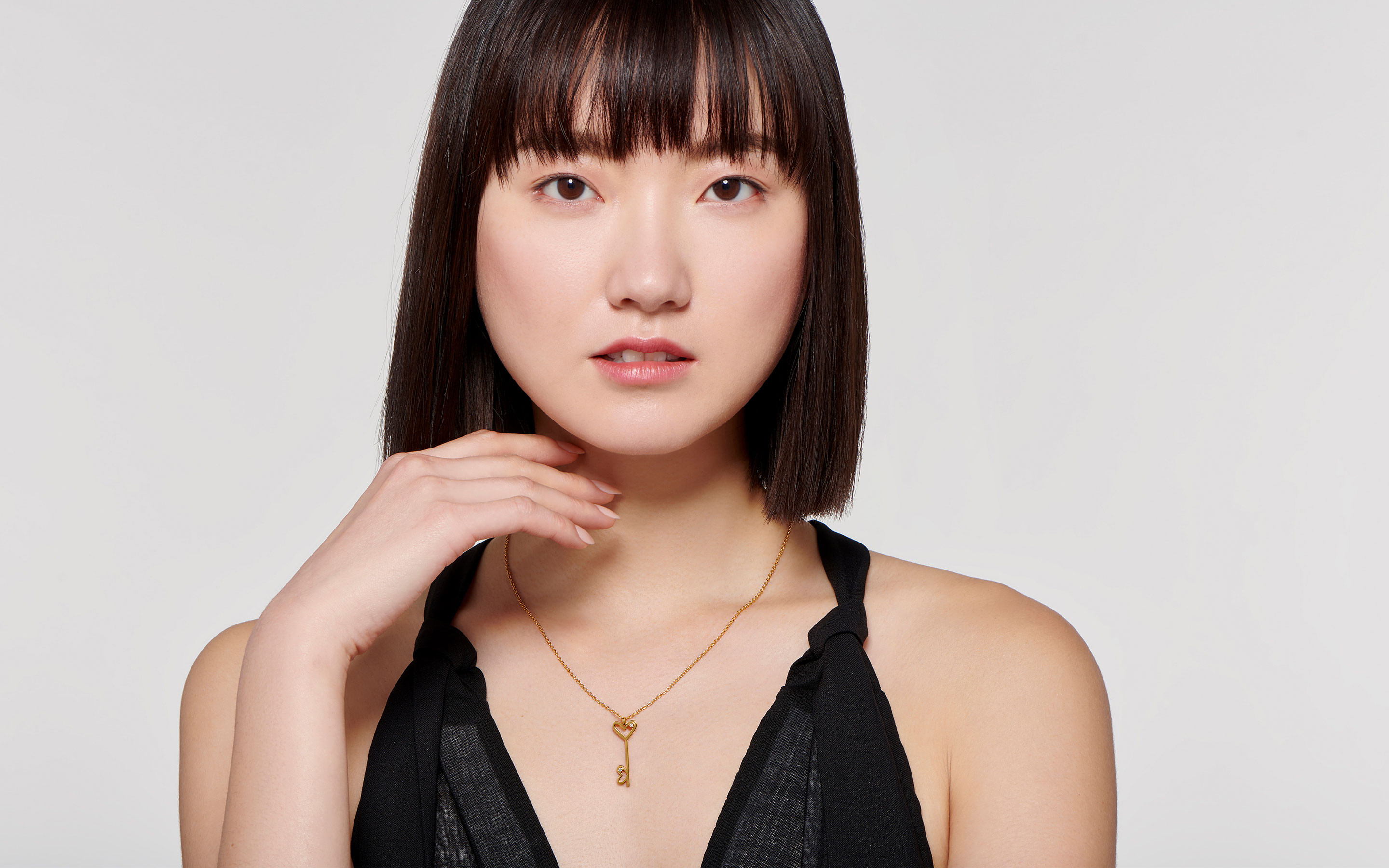 shining 22 karat gold necklace with double heart charm on gorgeous East Asian model