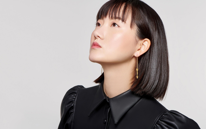 22 karat arrow-shaped gold earrings in threader style gracing beautiful East Asian model