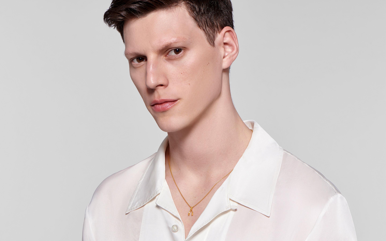 striking male model wearing trendy 22 karat gold necklace with wishbone charm