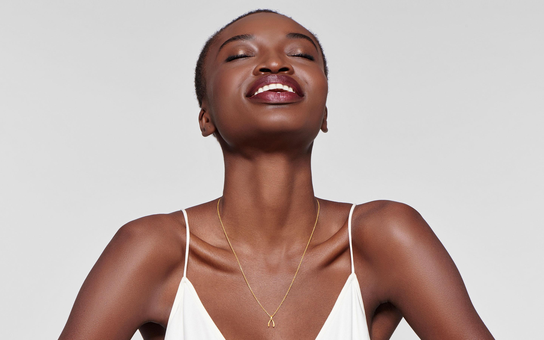 lustrous 22 karat gold necklace with wishbone pendant on glamorous black model