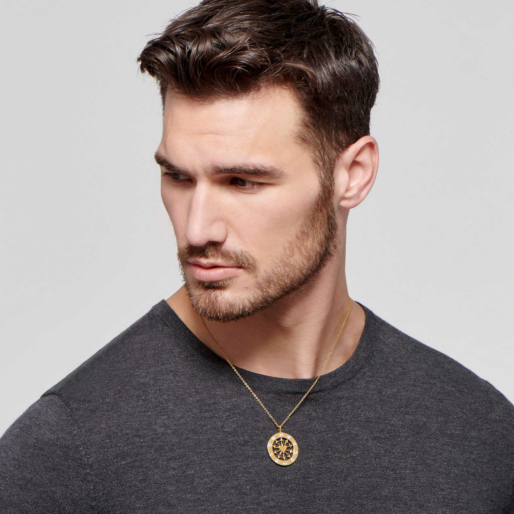 sculpted male model wearing medallion necklace made of 22 karat polished gold and studded with diamonds