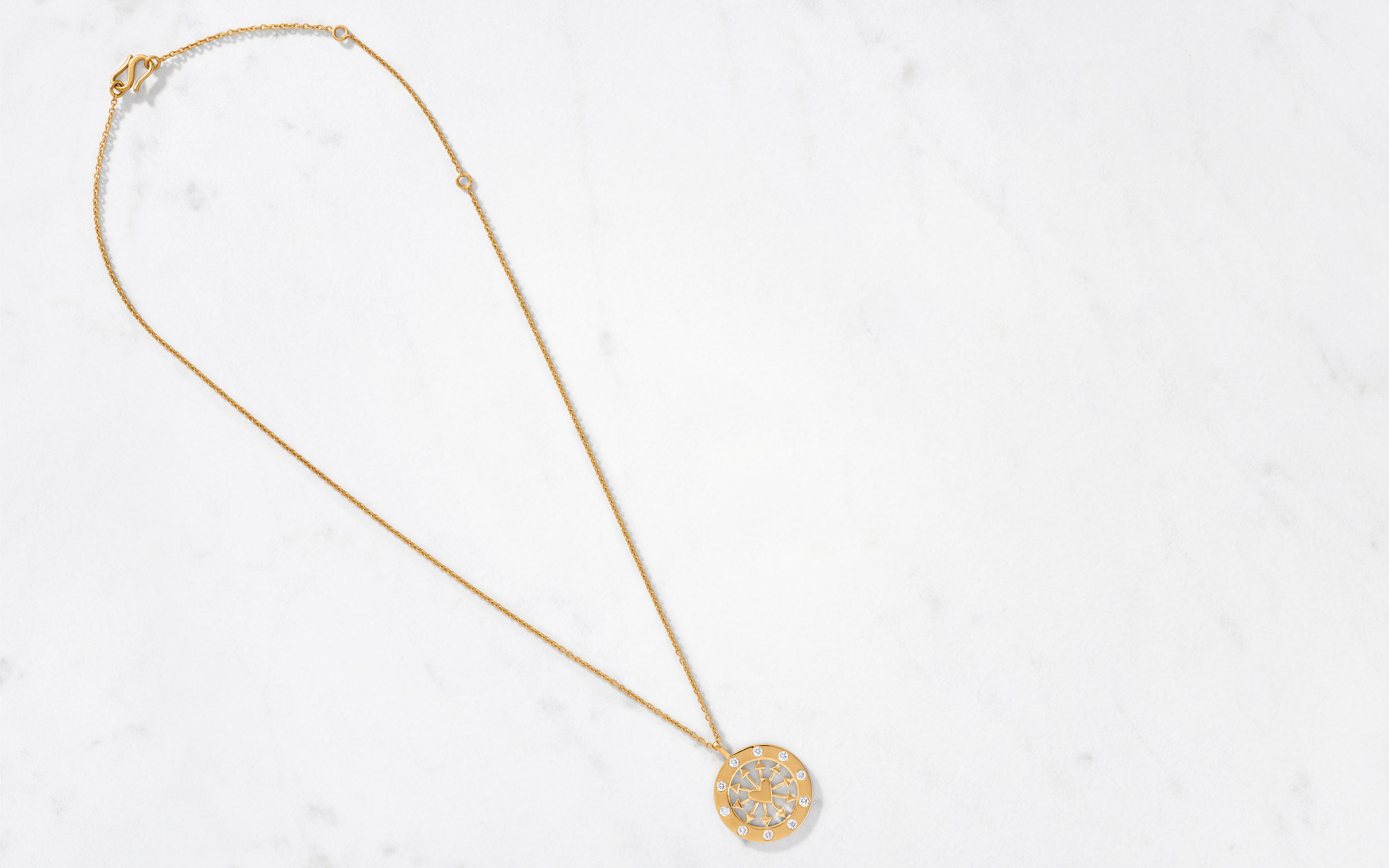 bright 22 karat gold necklace with medallion in heart and arrow shape including diamonds