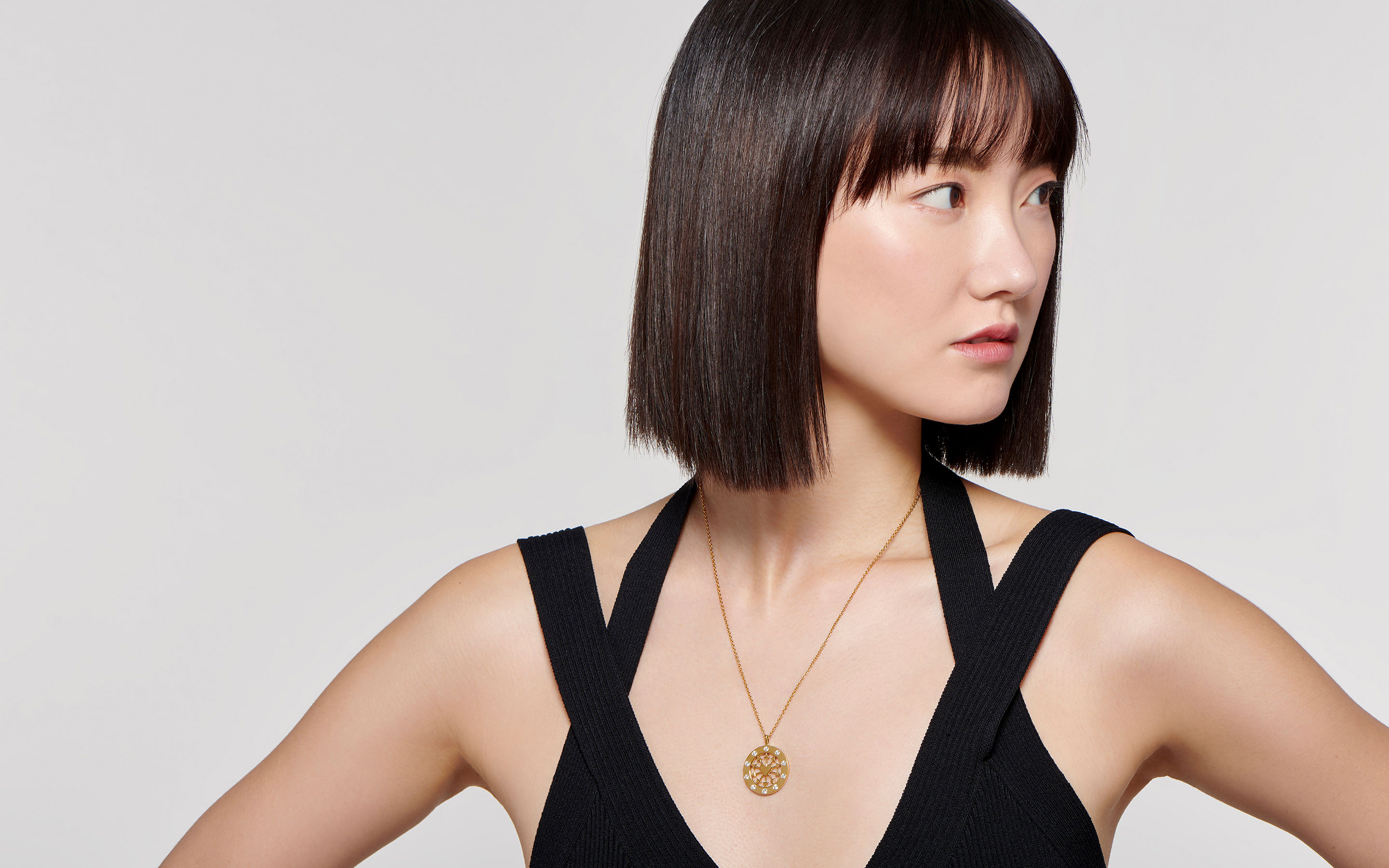elegant East Asian female model wearing sleek pendant medallion neck chain fashioned of 22 karat polished gold with diamonds