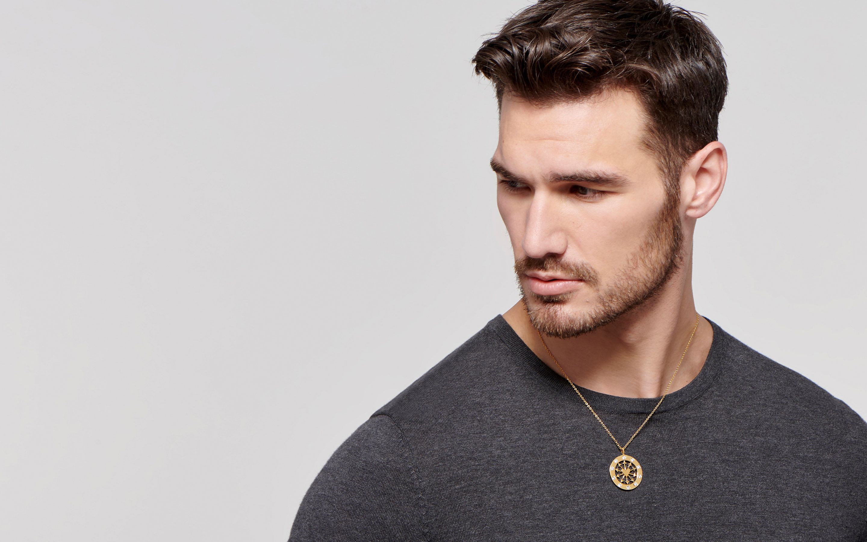 22 karat gold medallion necklace in heart and arrows shape with diamonds on dashing male model