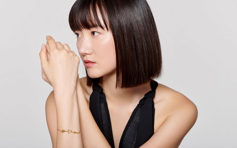brunette model wearing 22 karat gold heart and arrow charm bracelet