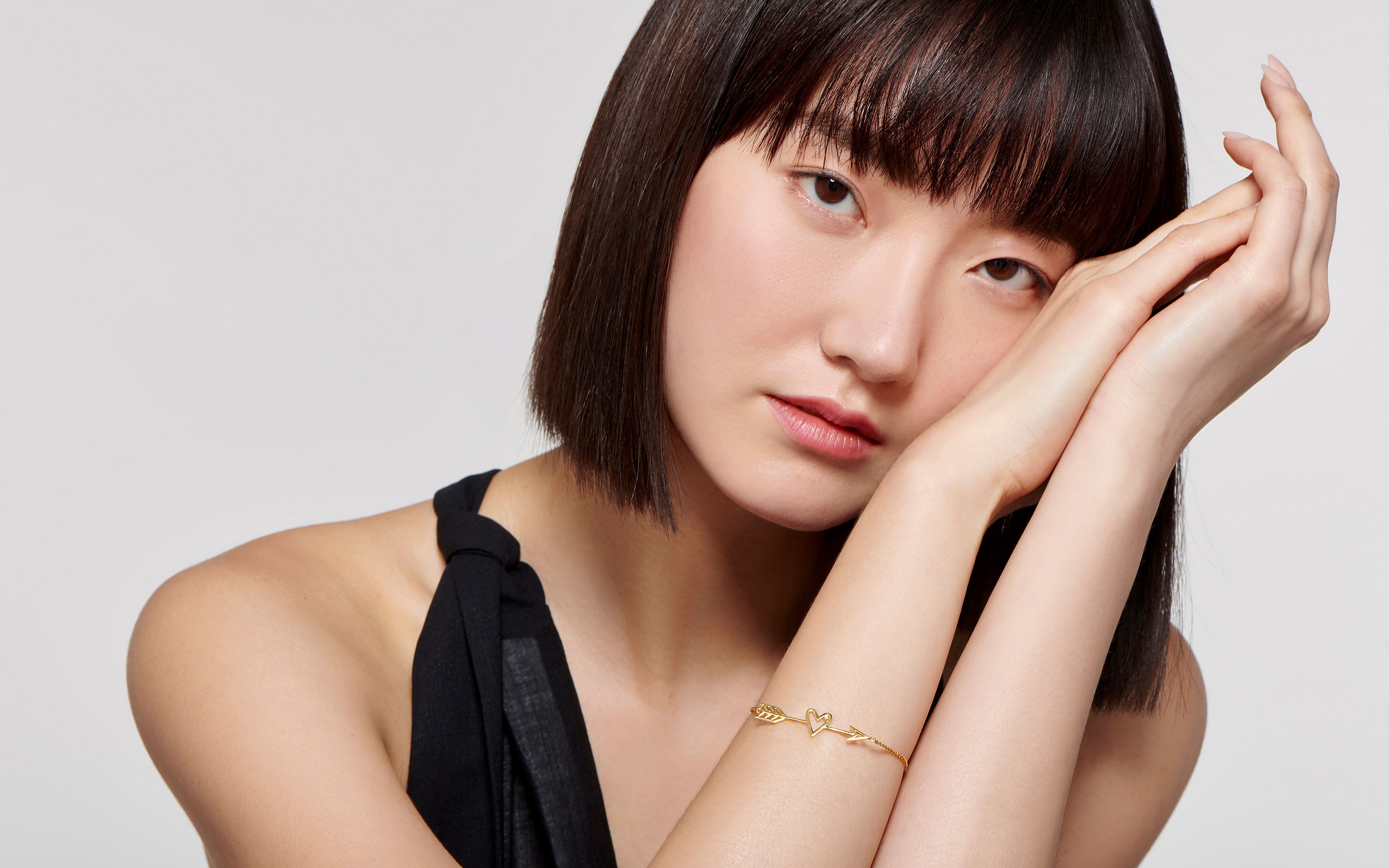 contemplative model sporting delicate 22 karat gold bracelet