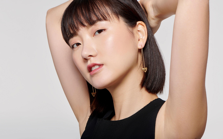 elegant East Asian female model with classic threader earrings in 22 karat gold