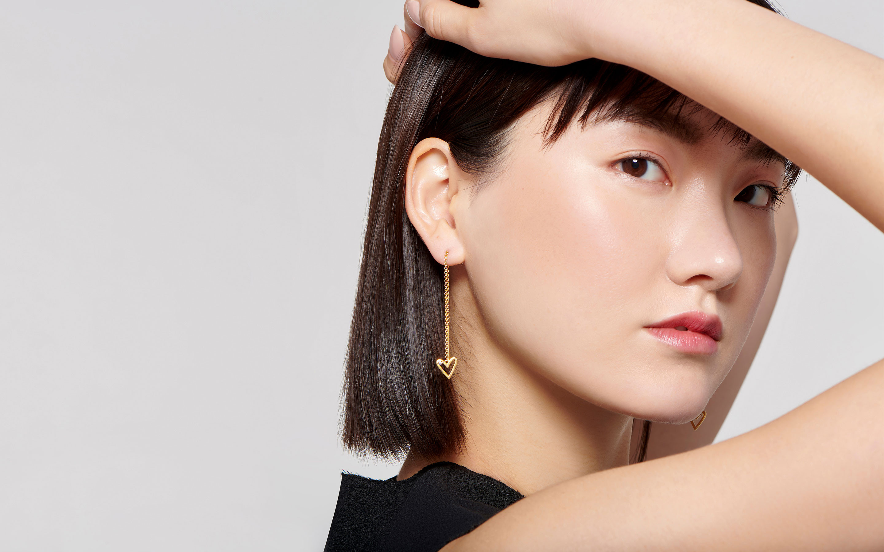 22 karat gold earrings in threader style with diamonds worn by attractive East Asian model in profile shot